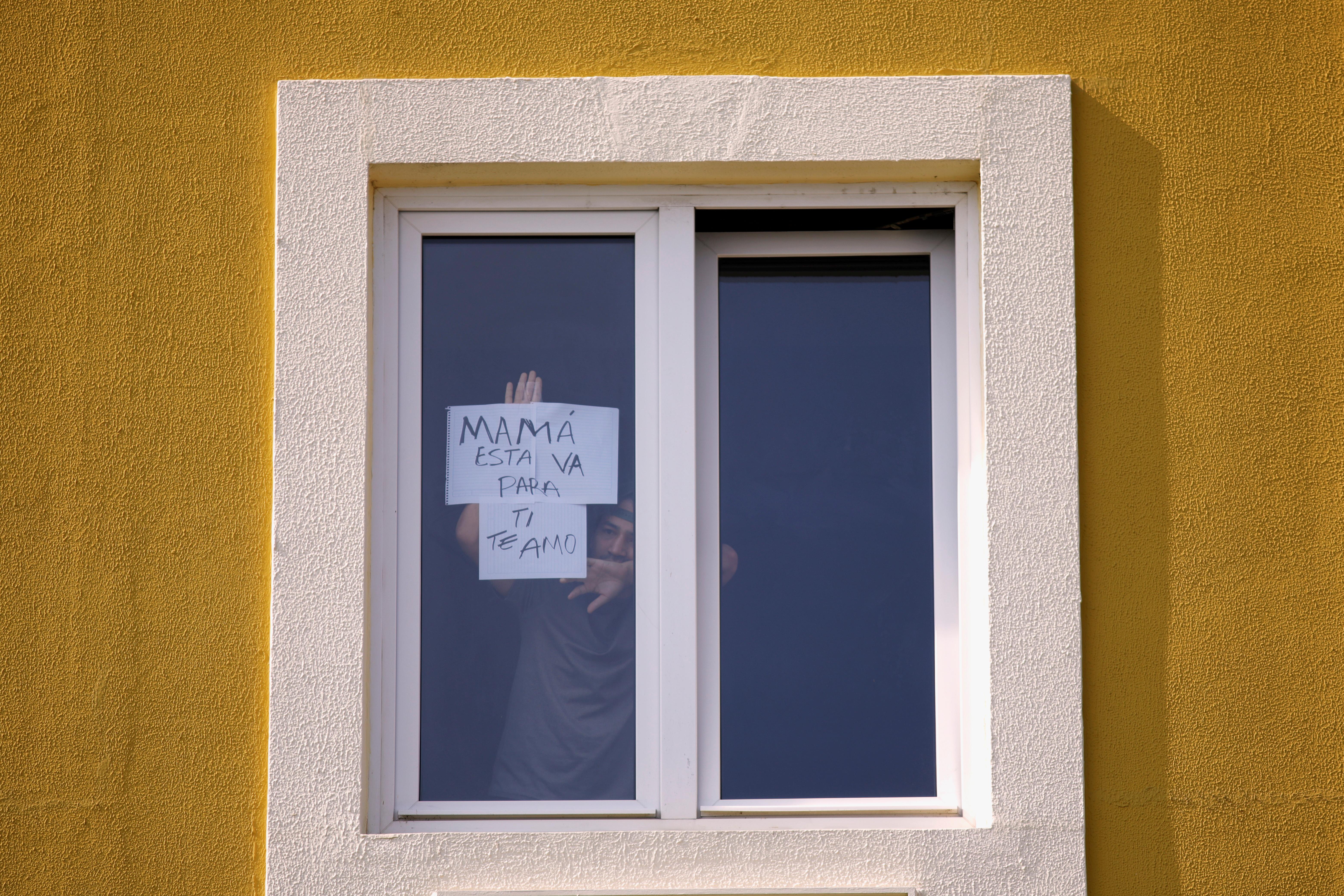Un paciente aislado en un hotel, utilizado como centro de cuarentena, muestra un letrero que dice en español: