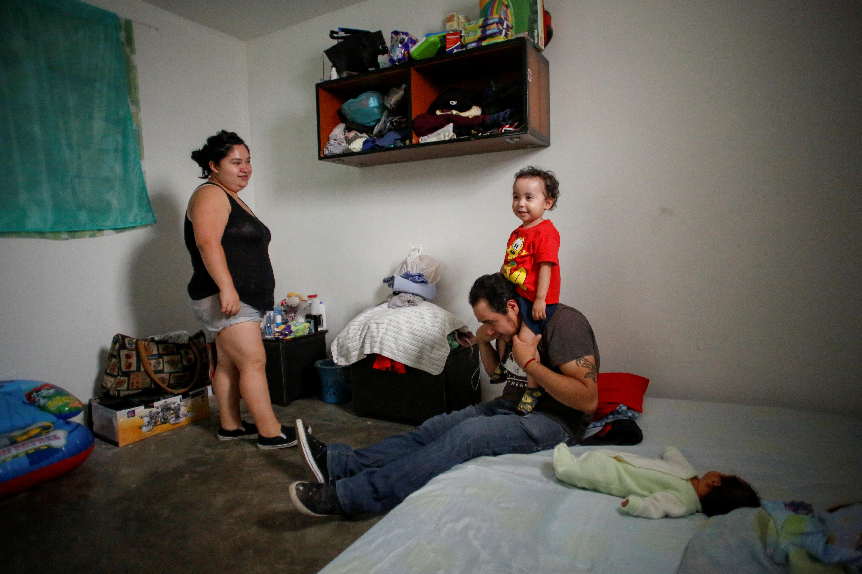 Karla López Rangel observa a su hijo Angel Flores López, de 3 años, sentado en los hombros de su esposo Miguel Flores Torres en su casa en Xochimilco, Ciudad de México , México, 17 de junio de 2020. Foto: REUTERS / Gustavo Graf.