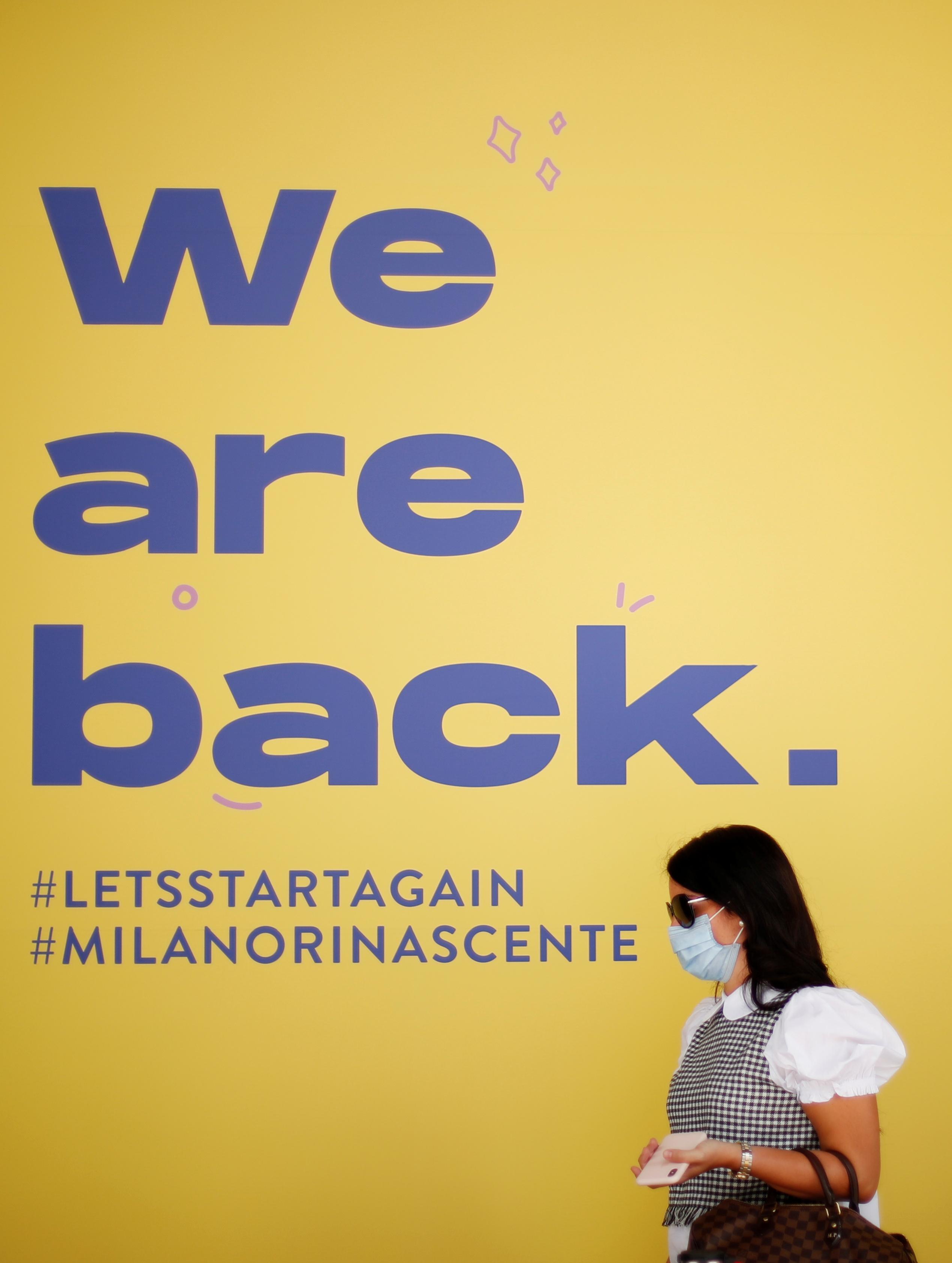 Una mujer pasa frente a un cartel que informa sobre la reapertura de un centro comercial en Milán (Reuters/ Alessandro Garofalo)