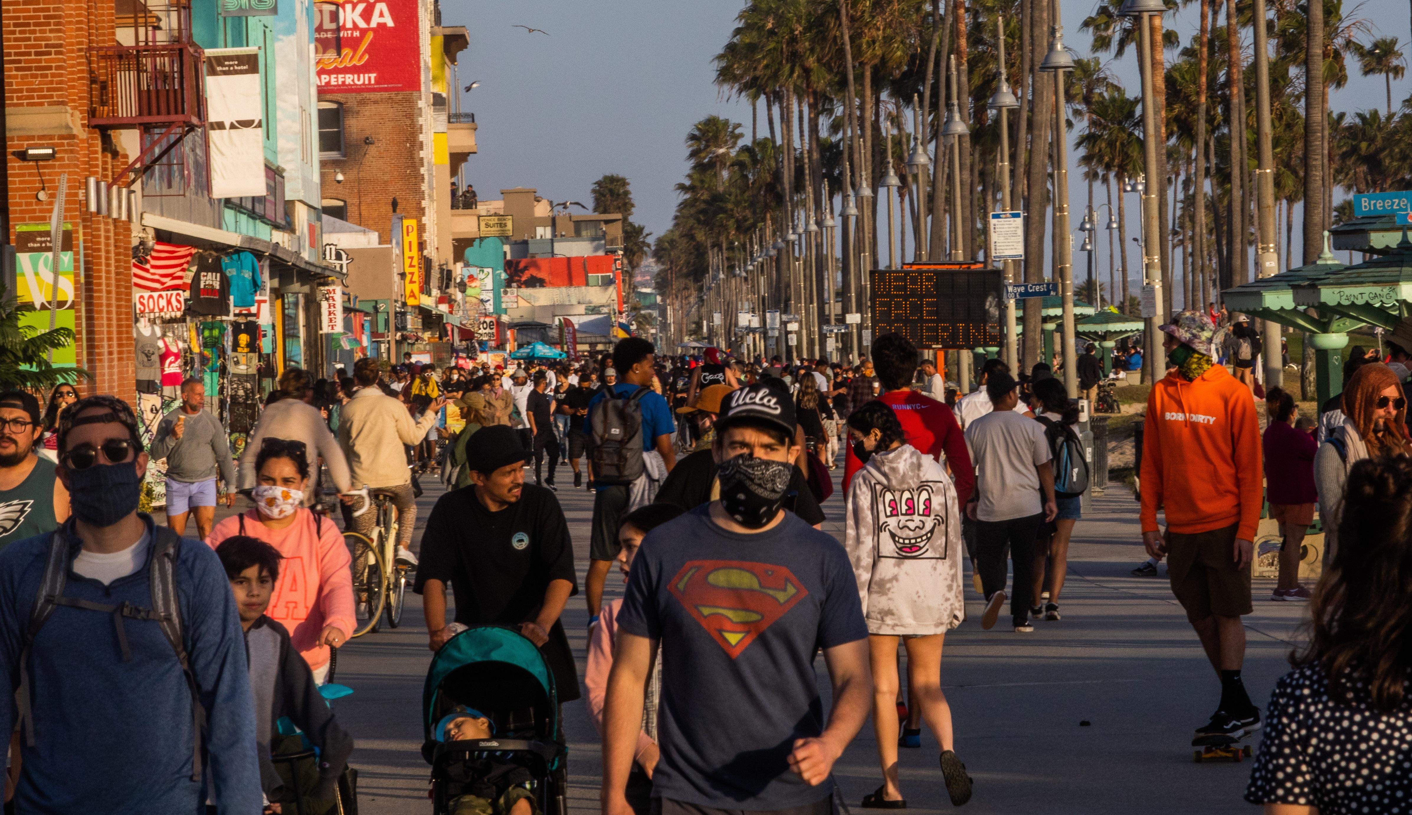 Una multitud en Venice Beach, algunos con mascarillas