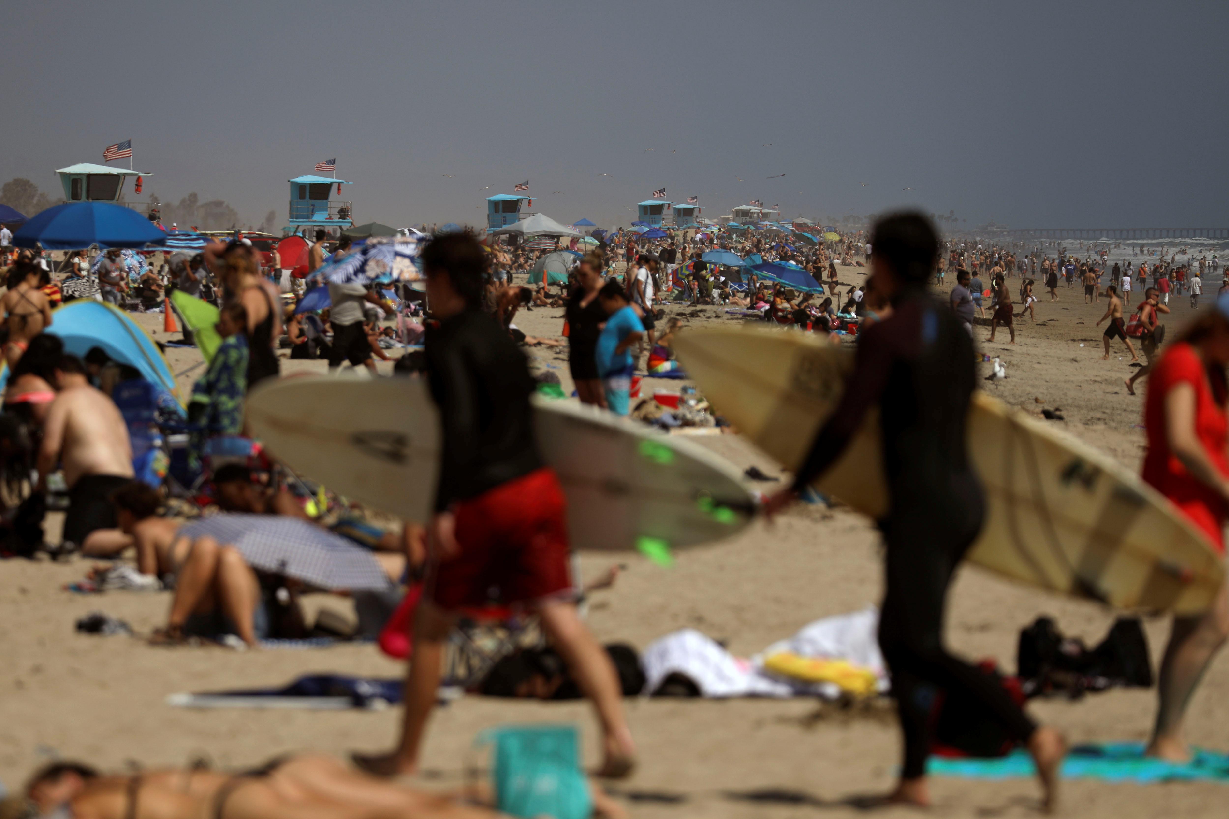 La arena llena de veraneantes en Huntington Beach, California