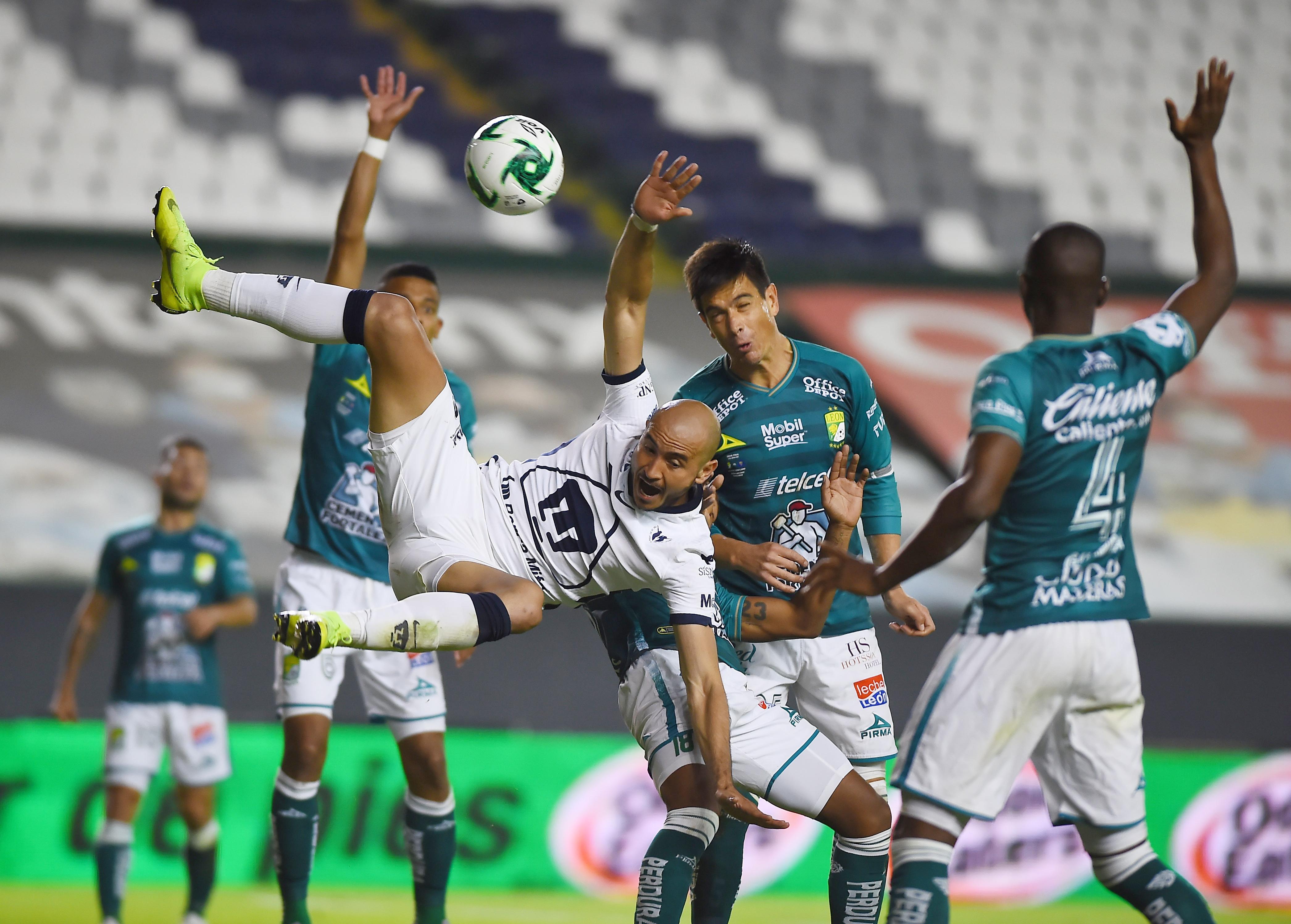 Carlos González en acción con Juan González de León. Estadio León, México. El 13 de diciembre de 2020.
