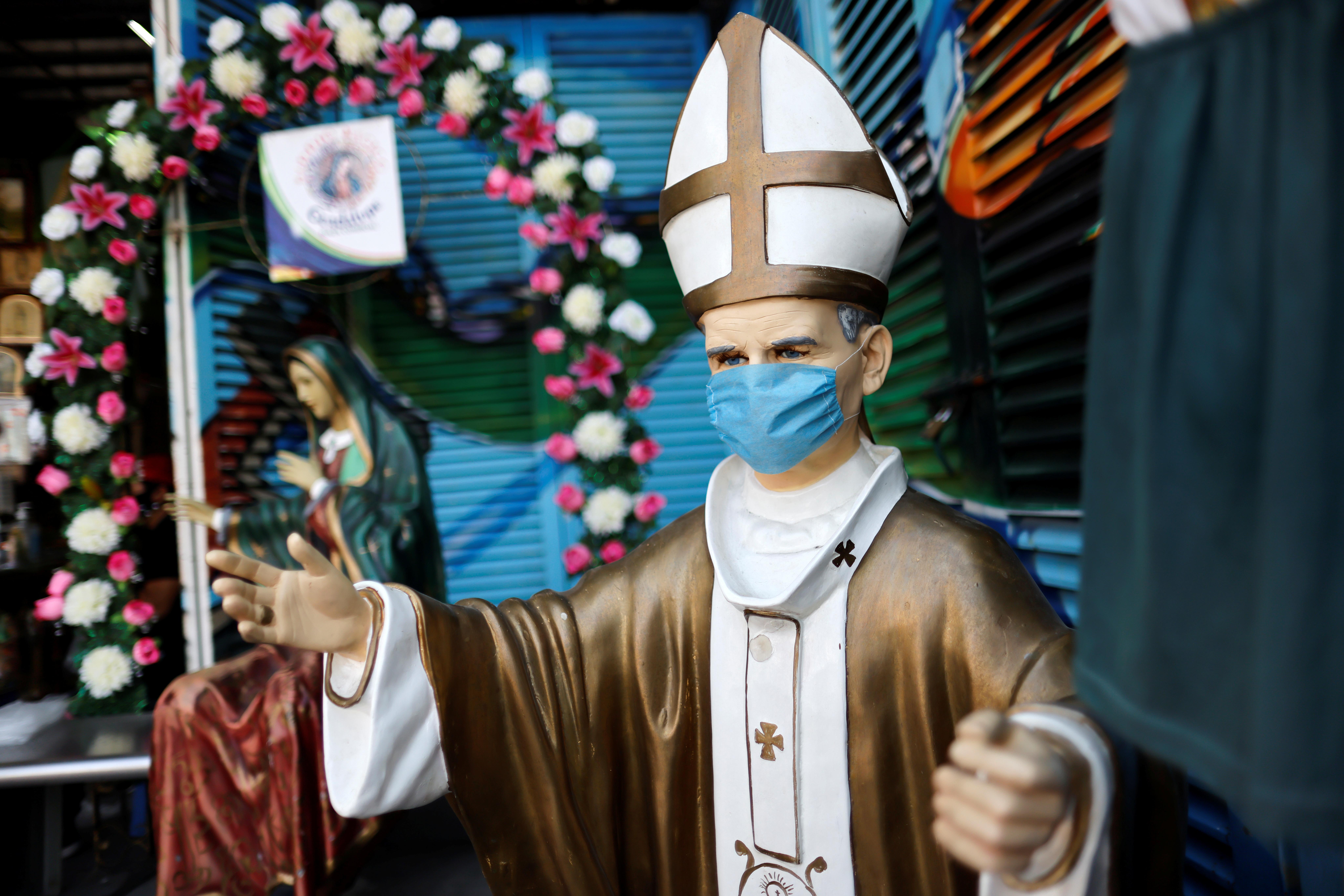 Una figura del difunto Papa Juan Pablo II con una máscara facial se ve cerca de la Basílica de Guadalupe que está temporalmente cerrada para evitar multitudes en el tradicional día de celebración de la Virgen de Guadalupe el 12 de diciembre, en la Ciudad de México, México, 10 de diciembre de 2020.