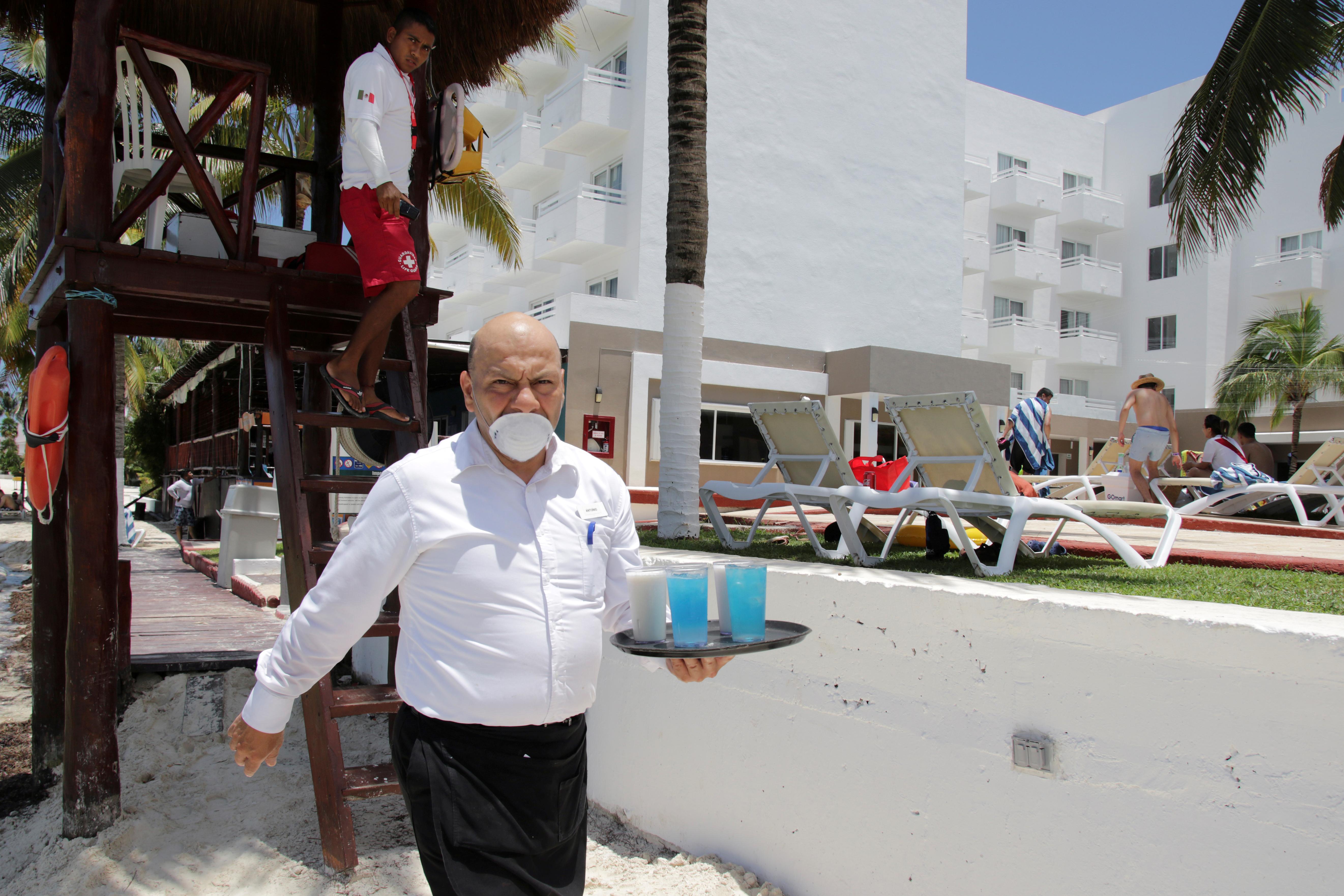 Un camarero usa una máscara protectora en un hotel después de que las autoridades locales impusieron estrictas medidas sanitarias para reabrir gradualmente a pesar de la pandemia de la enfermedad por coronavirus (COVID-19), en Cancún, México, 10 de junio de 2020. Fotografía tomada el 10 de junio de 2020. Foto: Reuters.