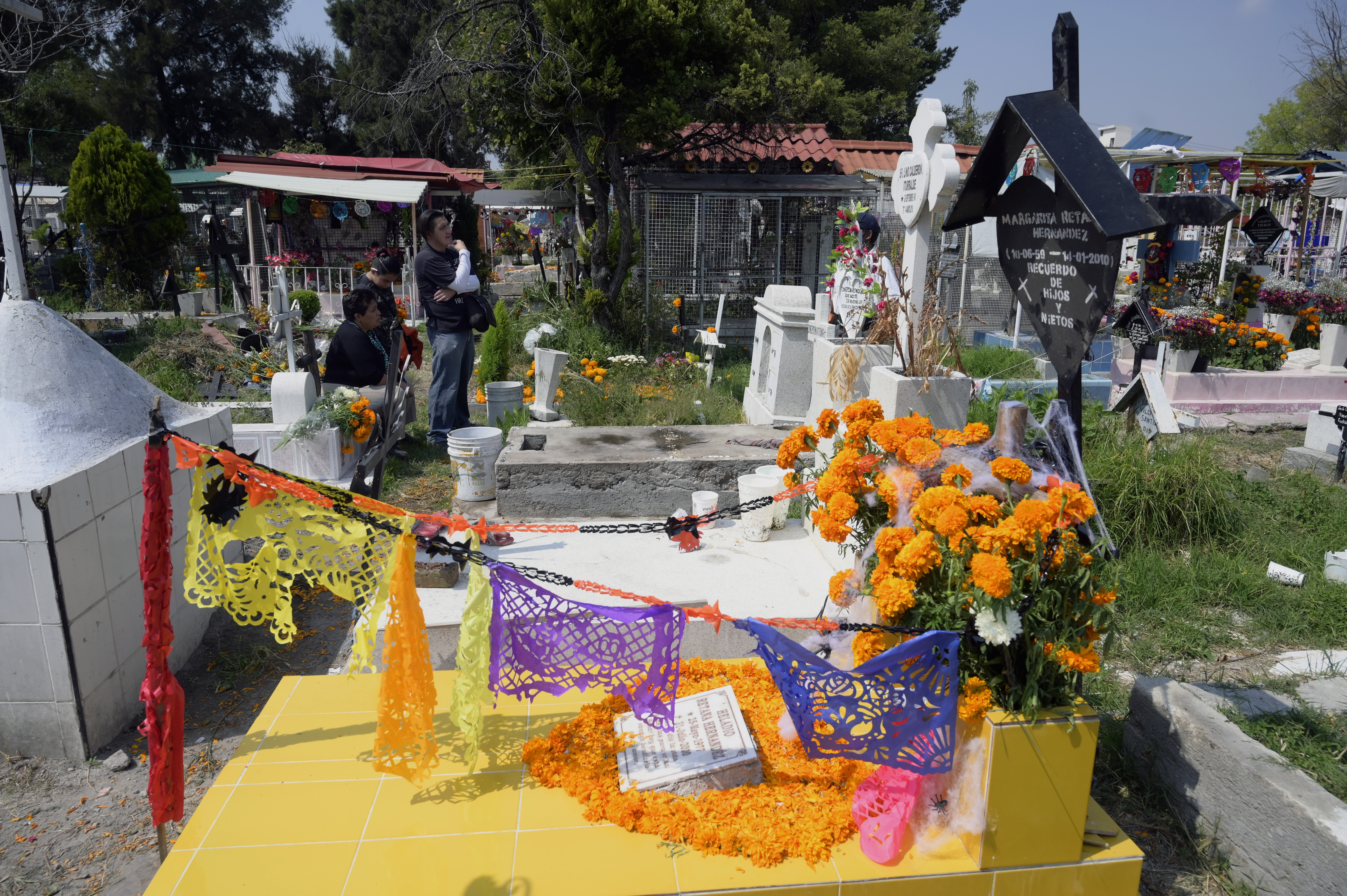 A family visit a relative's grave prior to the Day of the Dead at the Panteon San Jose, in Mexico City on October 28, 2020. - Due to the orange alert declared due to the Covid-19 pandemic, the authorities have decided to close the pantheons to visitors on November 1 and 2, the date that the dead are celebrated. (Photo by ALFREDO ESTRELLA / AFP)