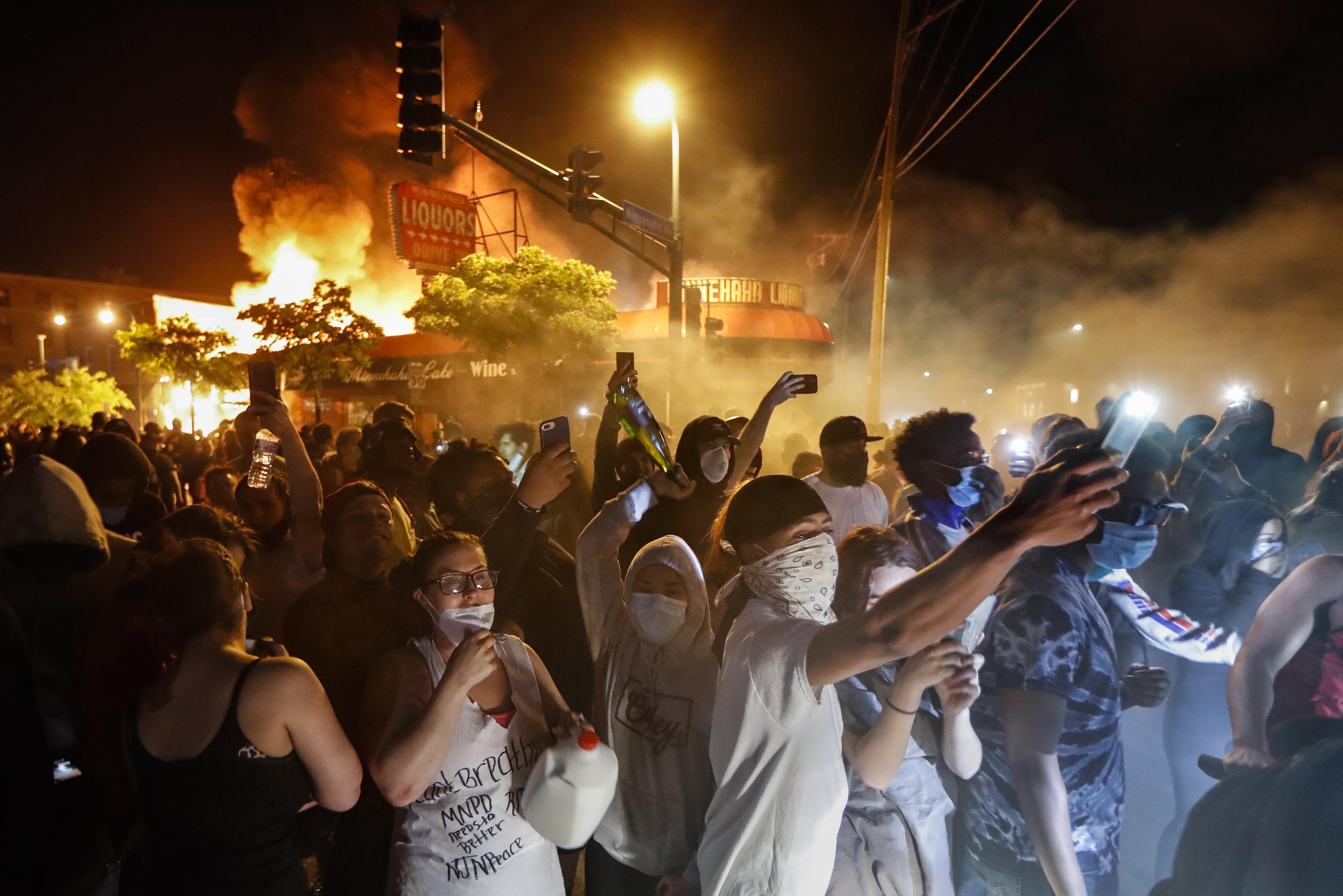 Manifestantes fuera de una tienda de licores en llamas en Minneapolis por la muerte de George Floyd (Foto AP/John Minchillo)