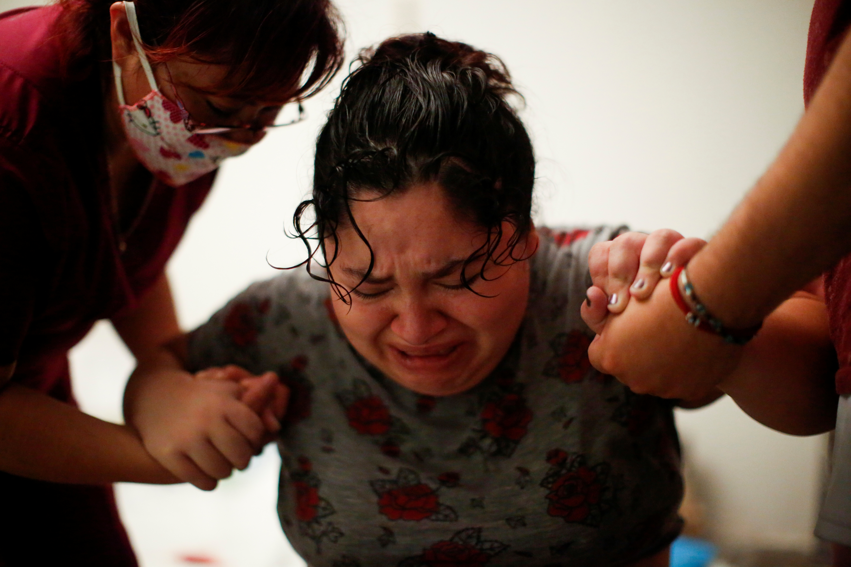 Karla López Rangel recibe el apoyo de su partera Luz Carrera López y su esposo Miguel Flores Torres mientras experimenta una contracción Foto: REUTERS / Gustavo Graf.