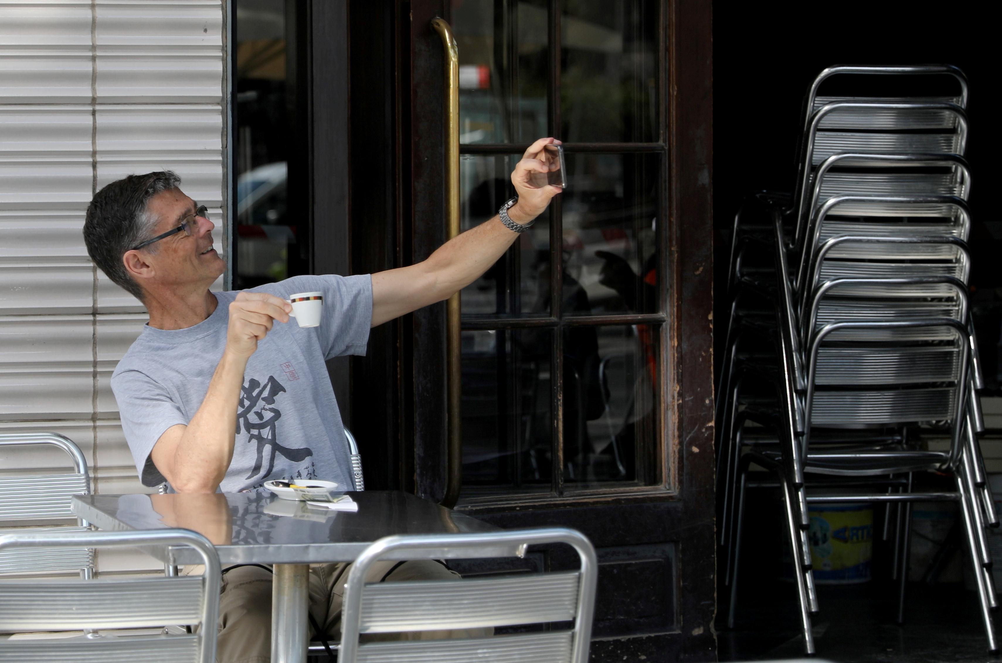 Un hombre se toma una selfie mientras toma un café en el bar Zurich de Plaza Catalunya en Barceolona (REUTERS/Nacho Doce)