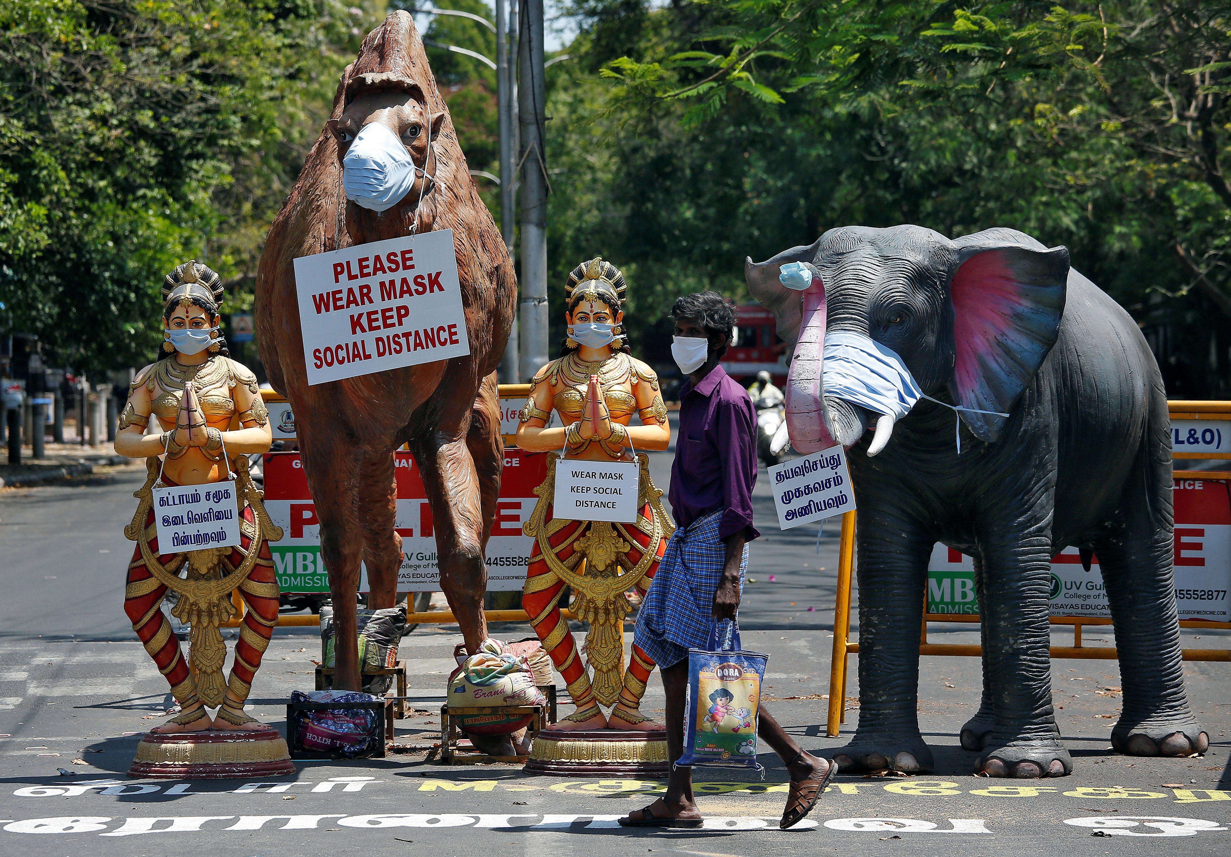 Un hombre con una máscara protectora pasa por delante de réplicas de animales y bailarines tradicionales instalados en un cruce de carretera, para crear conciencia sobre el uso de máscaras en Chennai, India, el 23 de abril de 2020. REUTERS/P. Ravikumar