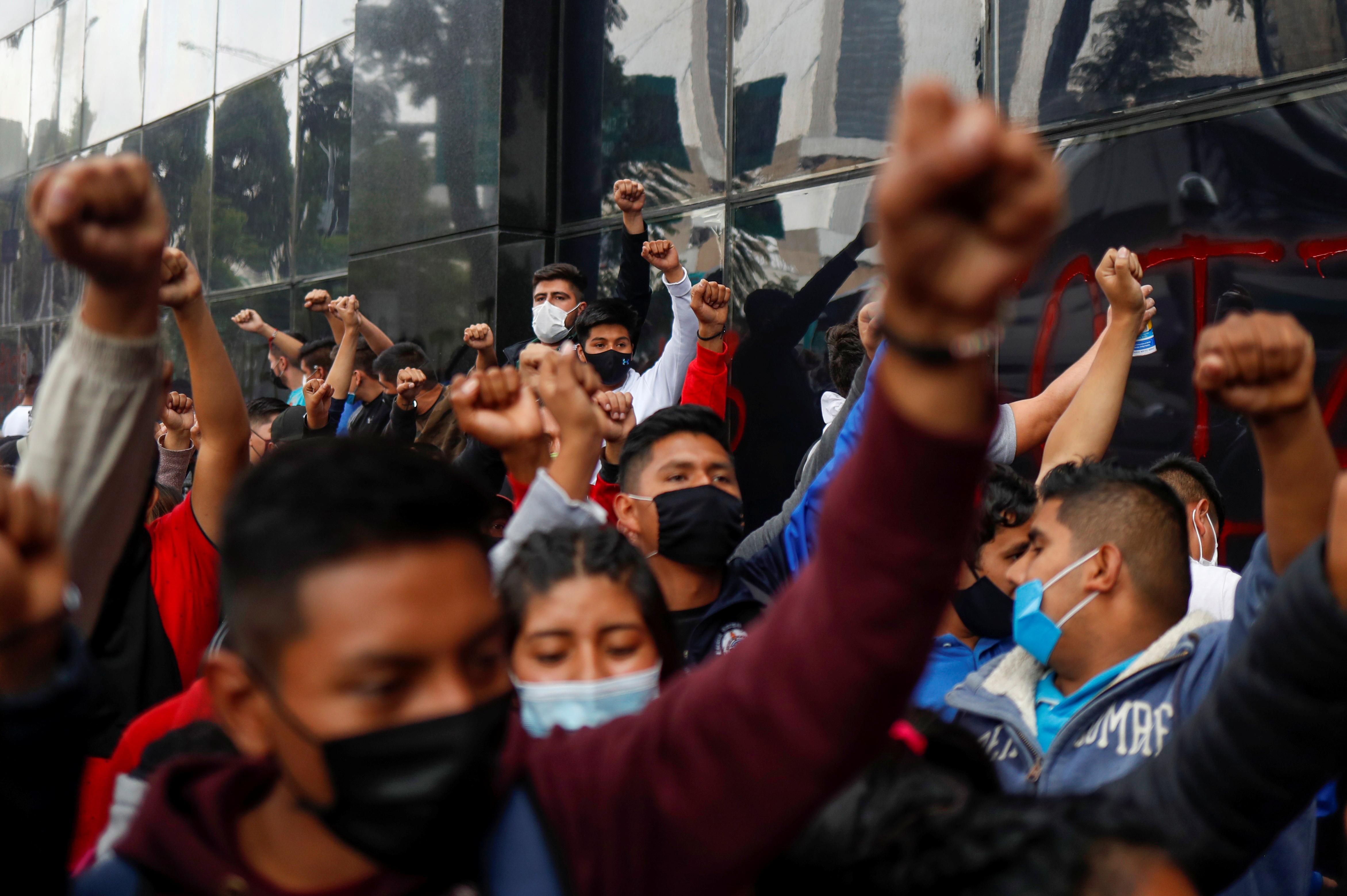 Estudiantes de la Escuela Normal Rural de Ayotzinapa levantan los puños durante una protesta frente a la Fiscalía General antes del sexto aniversario de la desaparición de 43 estudiantes, en la Ciudad de México, México, 25 de septiembre de 2020.