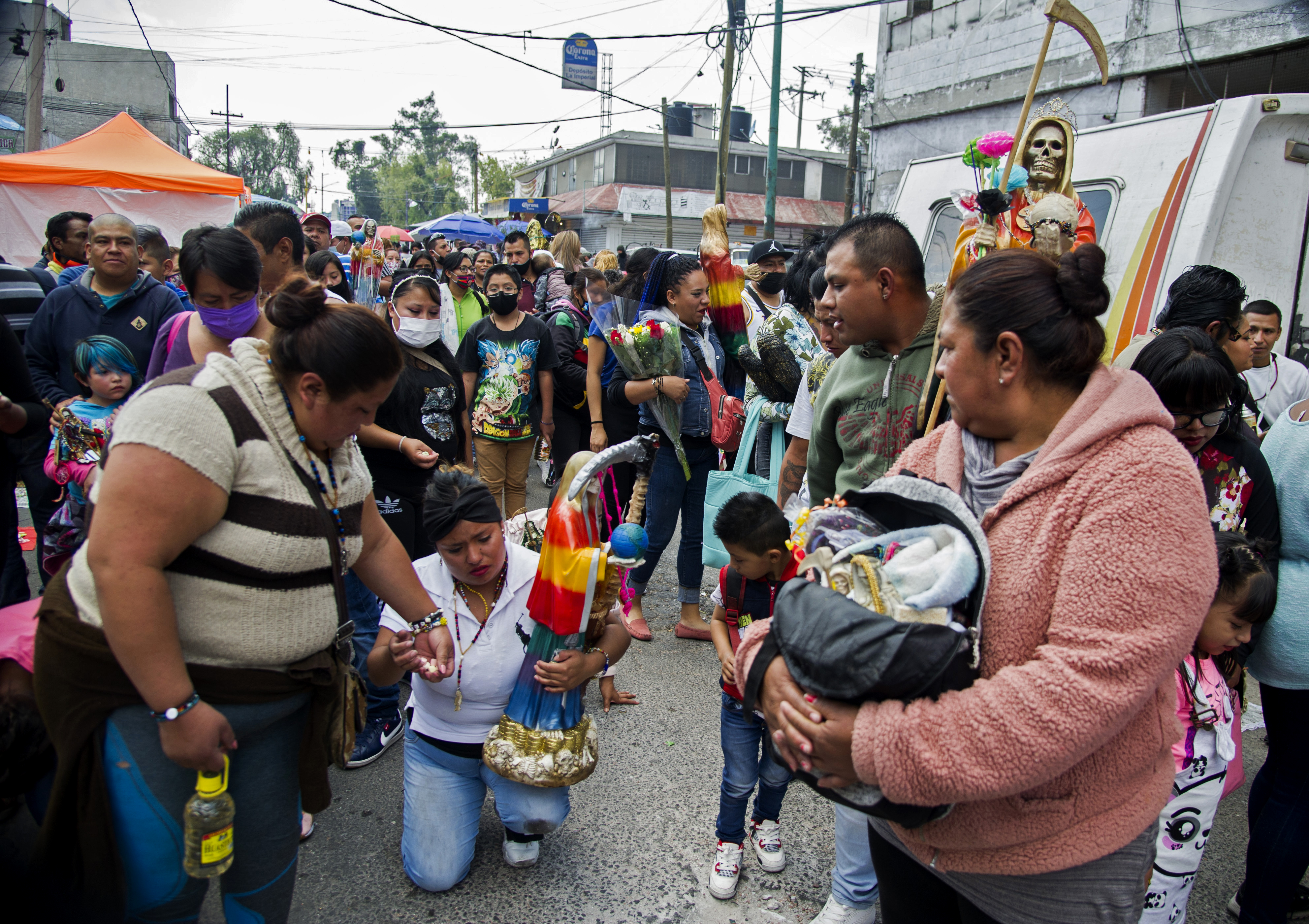 Una mujer camina de rodillas portando una figura de Santa Muerte frente a su santuario en la calle Alfarería, en el barrio de Tepito, de la Ciudad de México, el 1 de octubre de 2020