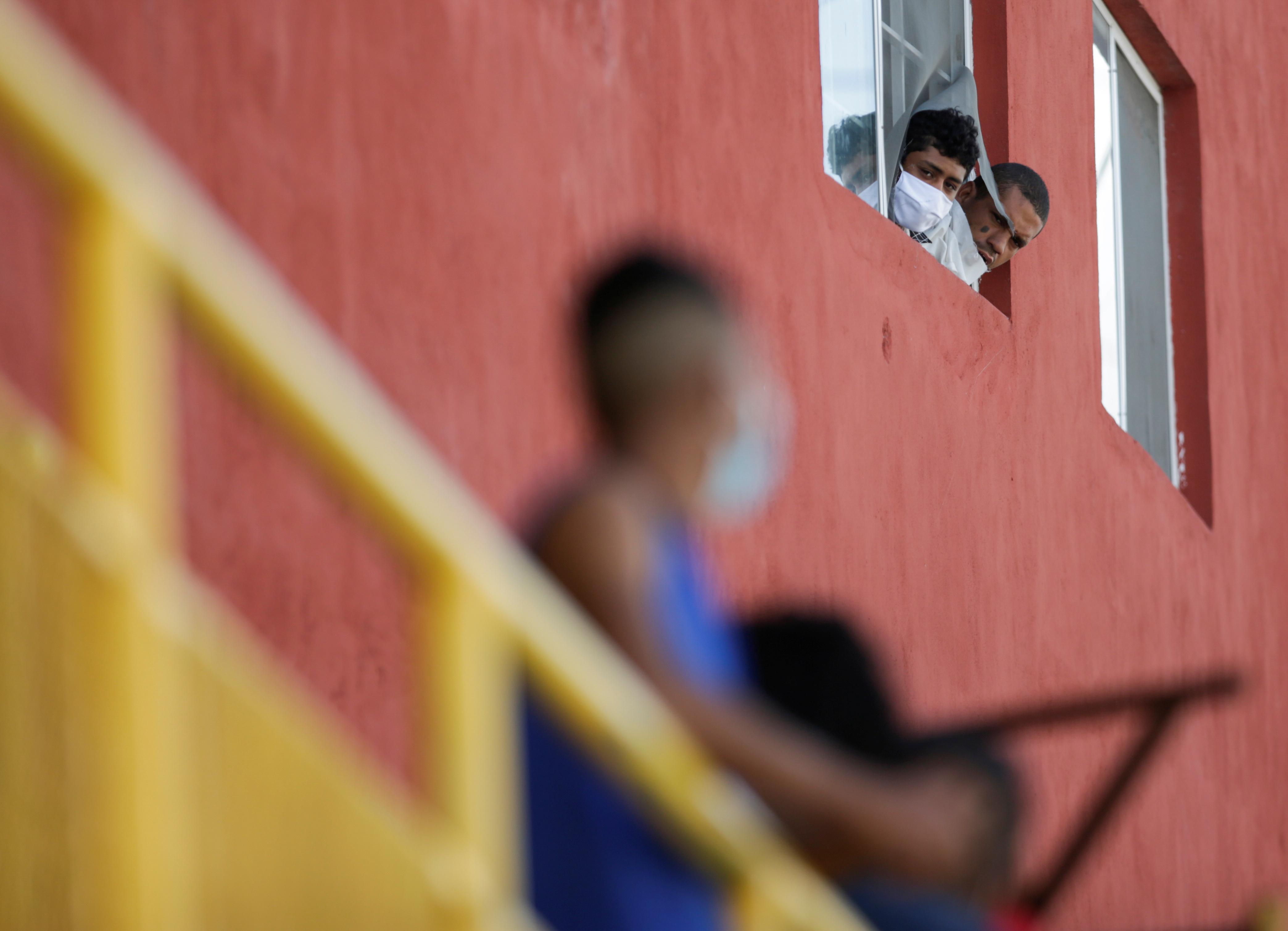 Los migrantes miran la calle desde una ventana en el refugio de migrantes