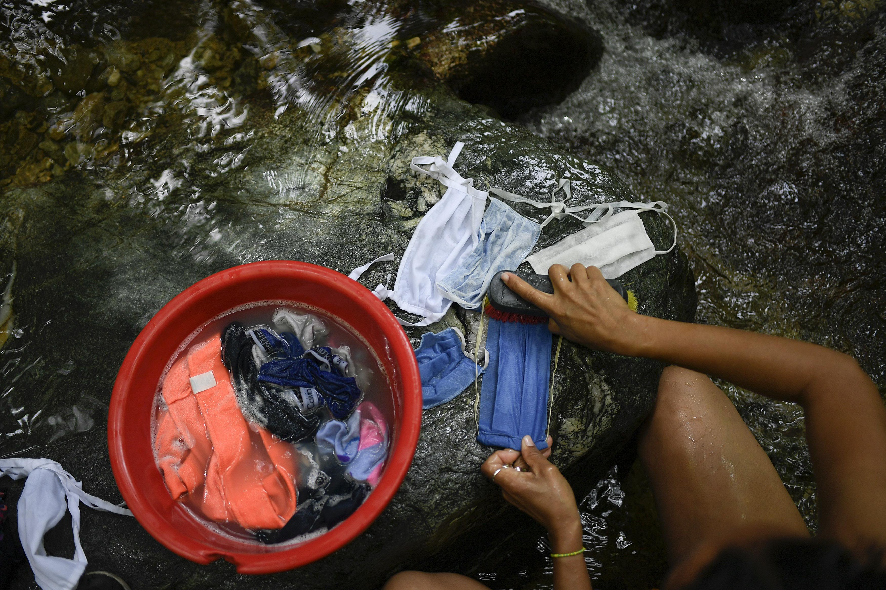 Una mujer lava sus mascarillas con agua corriente de la montaña Ávila, en Caracas, Venezuela, el 21 de junio de 2020. La crisis de agua no es nada nuevo en Venezuela, pero el agua es todavía más importante hoy en día por la pandemia del coronavirus. (AP Foto/Matías Delacroix)