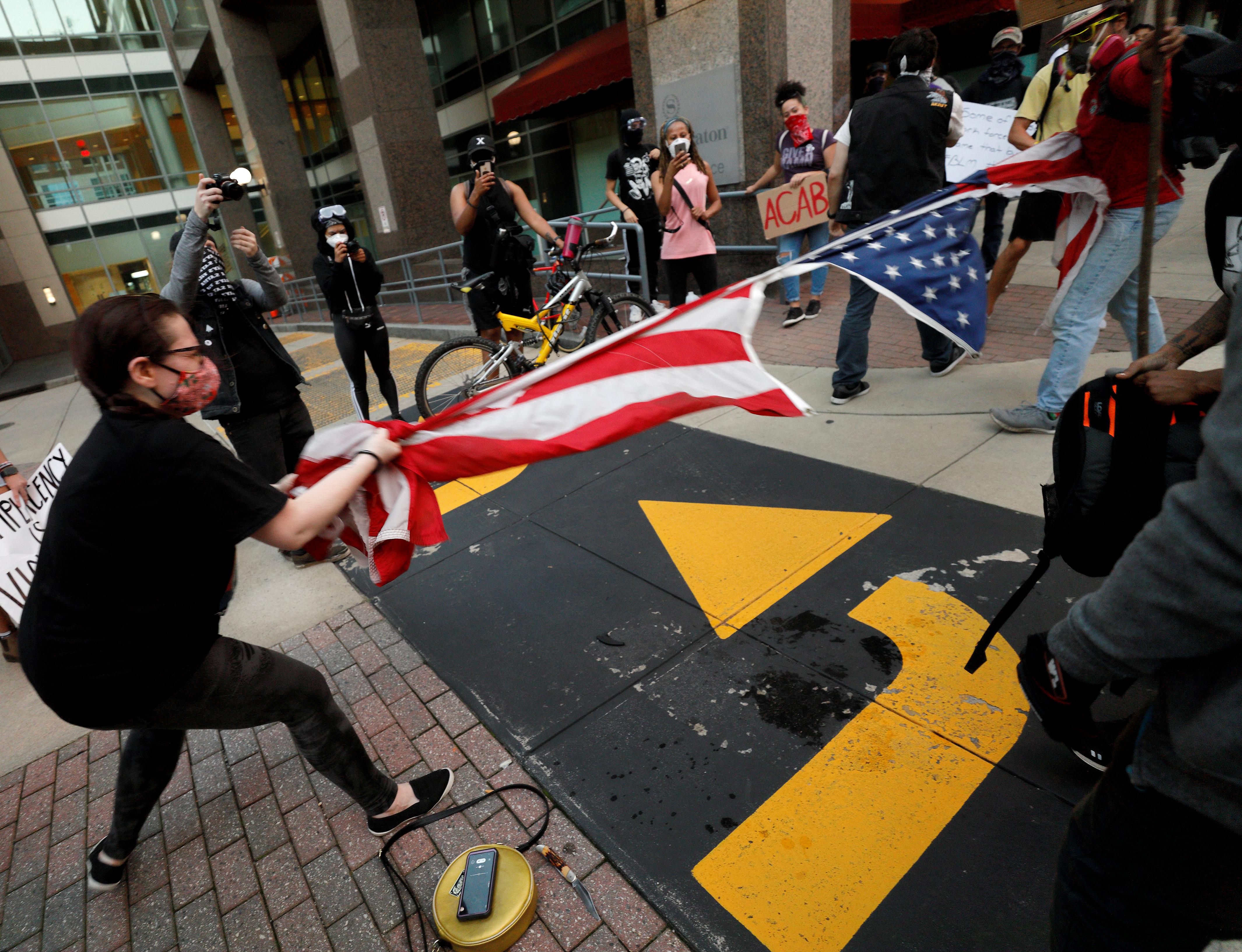 Manifestantes rompen bandera de EEUU