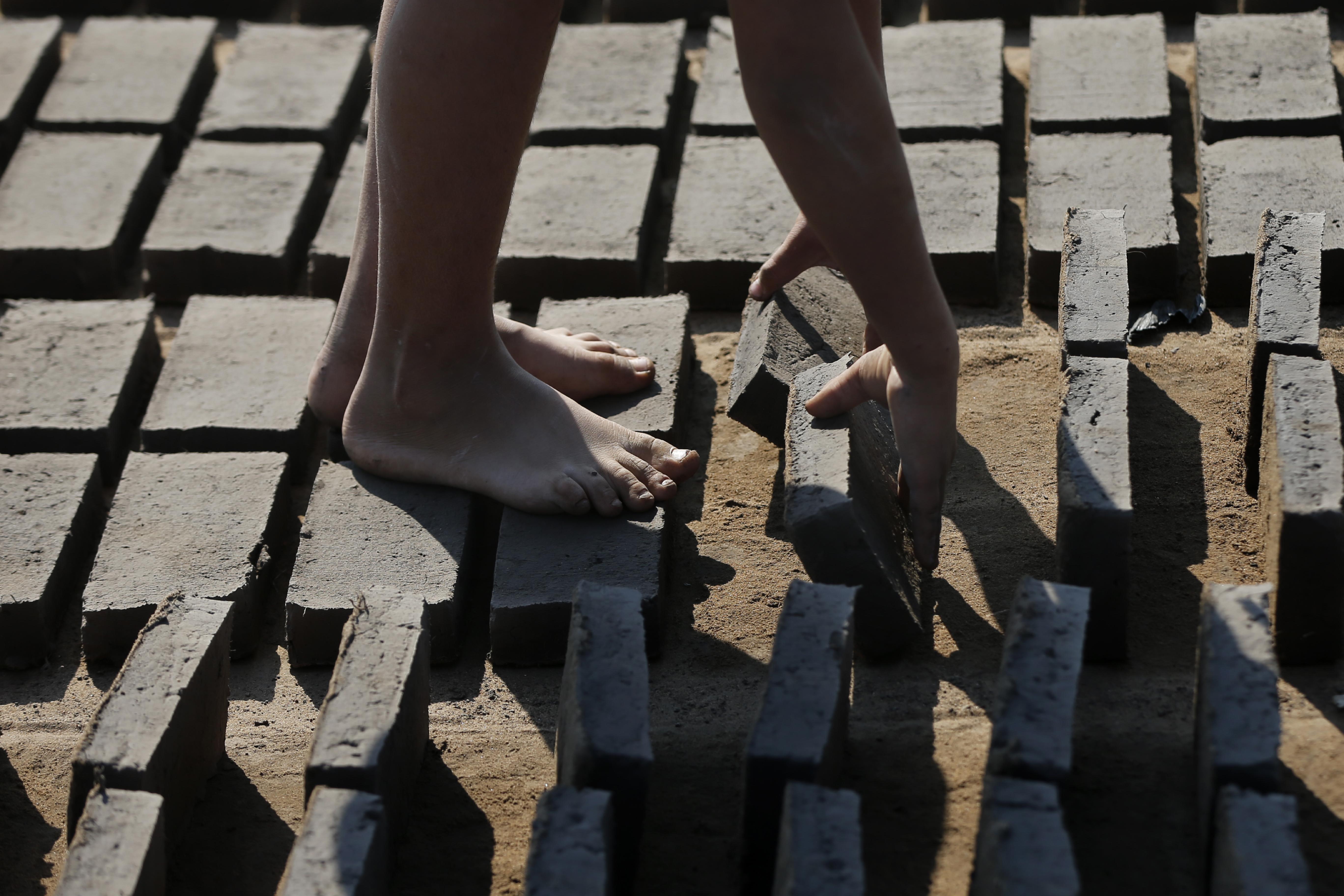 Cristian voltea ladrillos de arcilla de lado mientras se secan al sol antes de colocarlos en un horno en una pequeña fábrica de ladrillos en Tobati, Paraguay, el lunes 24 de agosto de 2020.