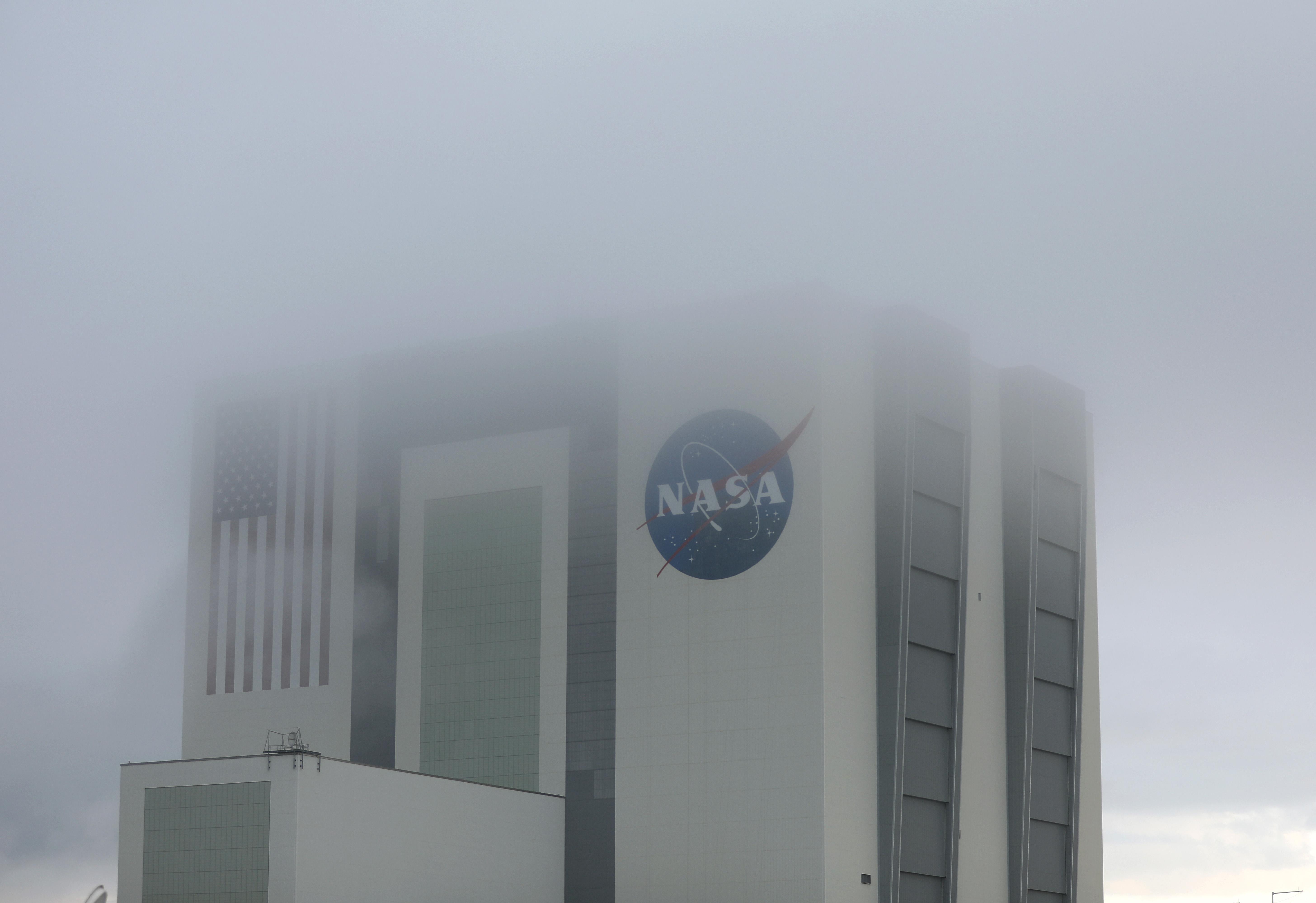 Nubes bajas rodean el edificio de ensamblaje de vehículos de la NASA mientras se prepara para lanzar el cohete SpaceX Falcon 9 con la nave espacial Crew Dragon acoplada desde la plataforma de lanzamiento 39A en el Centro Espacial Kennedy el 27 de mayo de 2020 en Cabo Cañaveral, Florida (Joe Raedle/Getty Images/AFP)