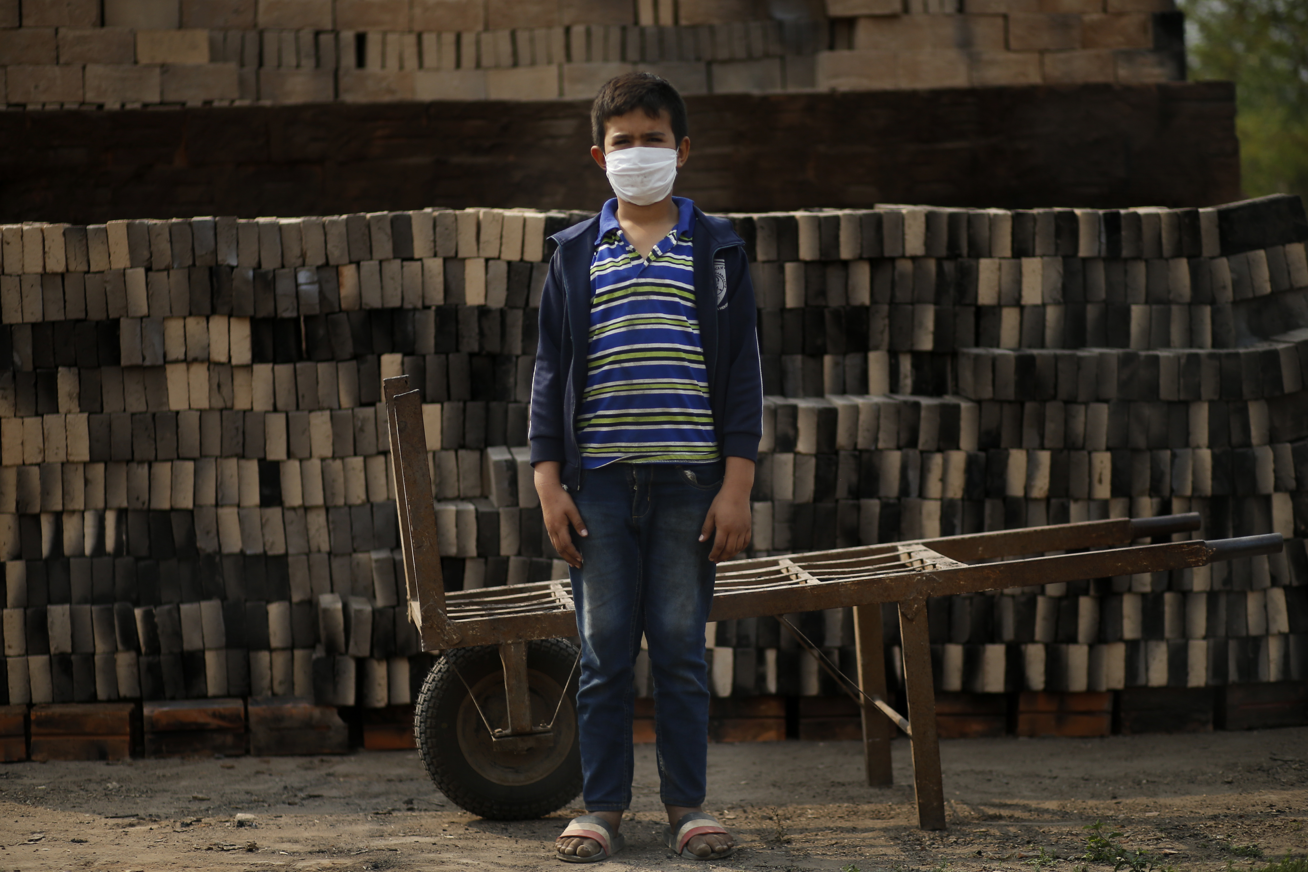 Ronnie, de 10 años, con una máscara para frenar la propagación del nuevo coronavirus, posa para un retrato mientras trabaja junto a su padre en una pequeña fábrica de ladrillos en Tobati, Paraguay, el lunes 31 de agosto de 2020.