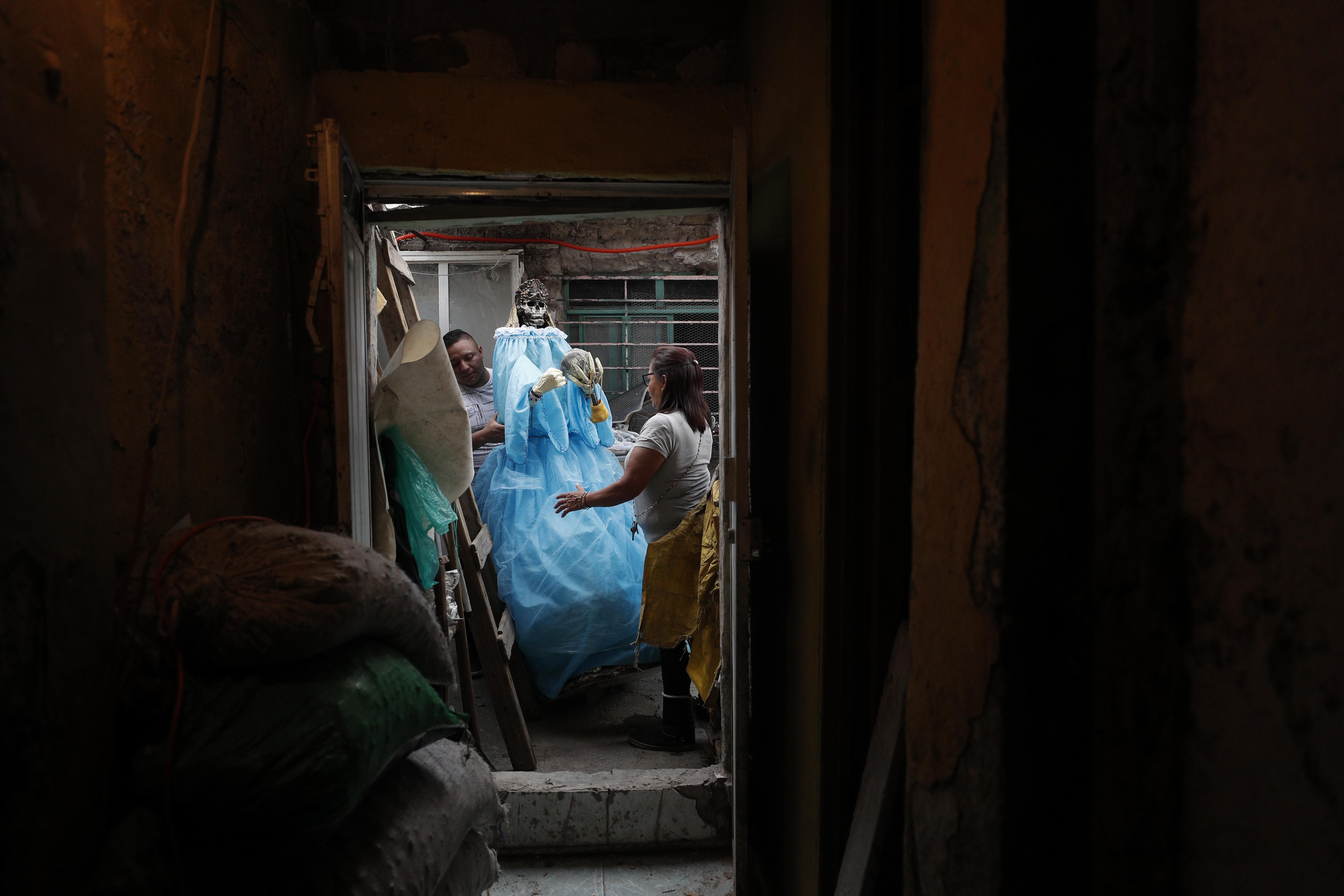 Elvia Sánchez Díaz, de 55 años, recibe ayuda de un vecino para devolver una figura gigante de Santa Muerte a su casa. (Foto: AP / Rebecca Blackwell )