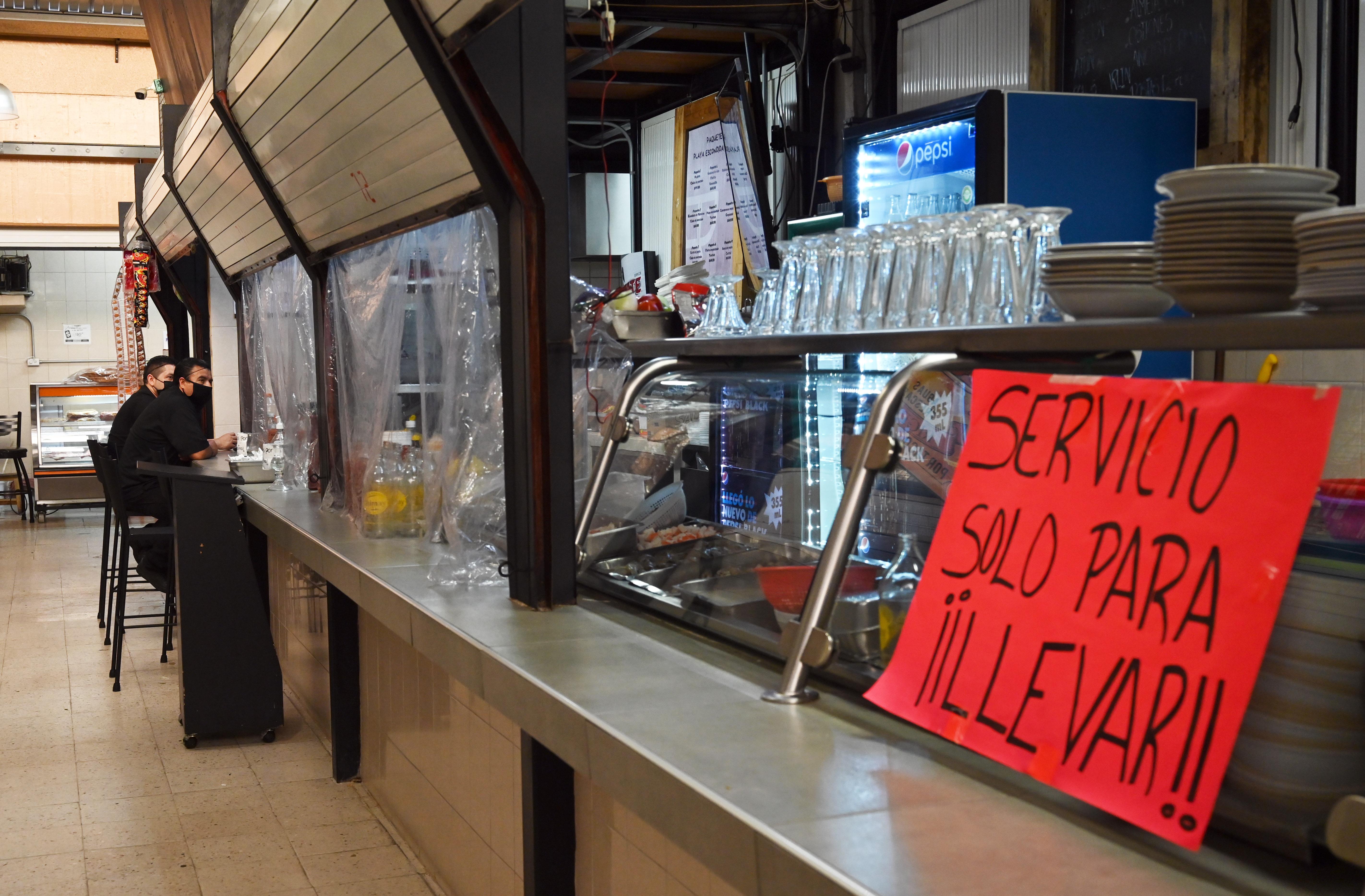 Los empleados de un restaurante esperan a los clientes mientras permanece cerrado al público en un mercado popular en la Ciudad de México el 29 de junio de 2020. (Foto: RODRIGO ARANGUA / AFP)