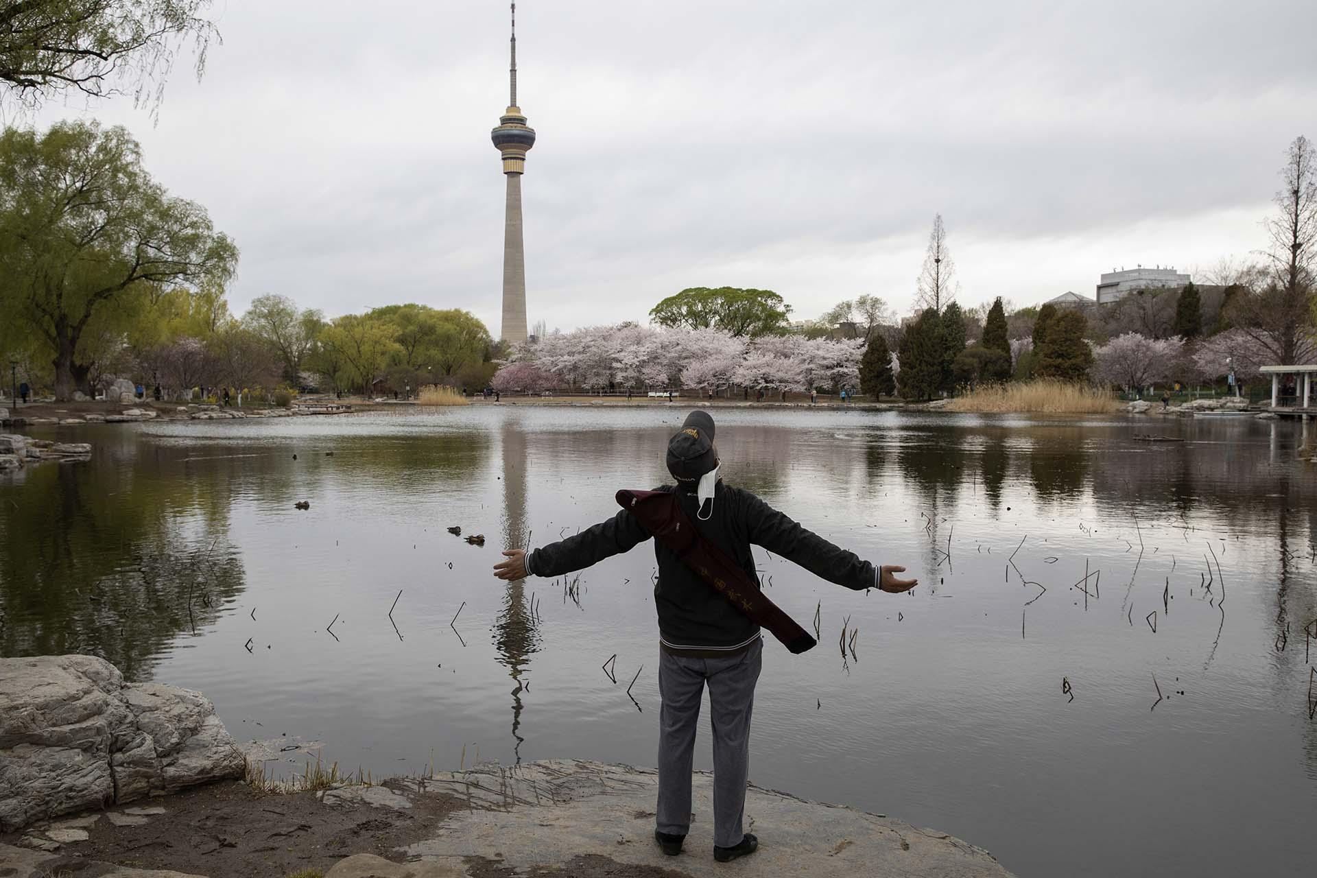 Un hombre se quita su máscara facial y respira mirando al cielo en el Parque Yuyuantan en Beijing (AP Photo/Ng Han Guan)