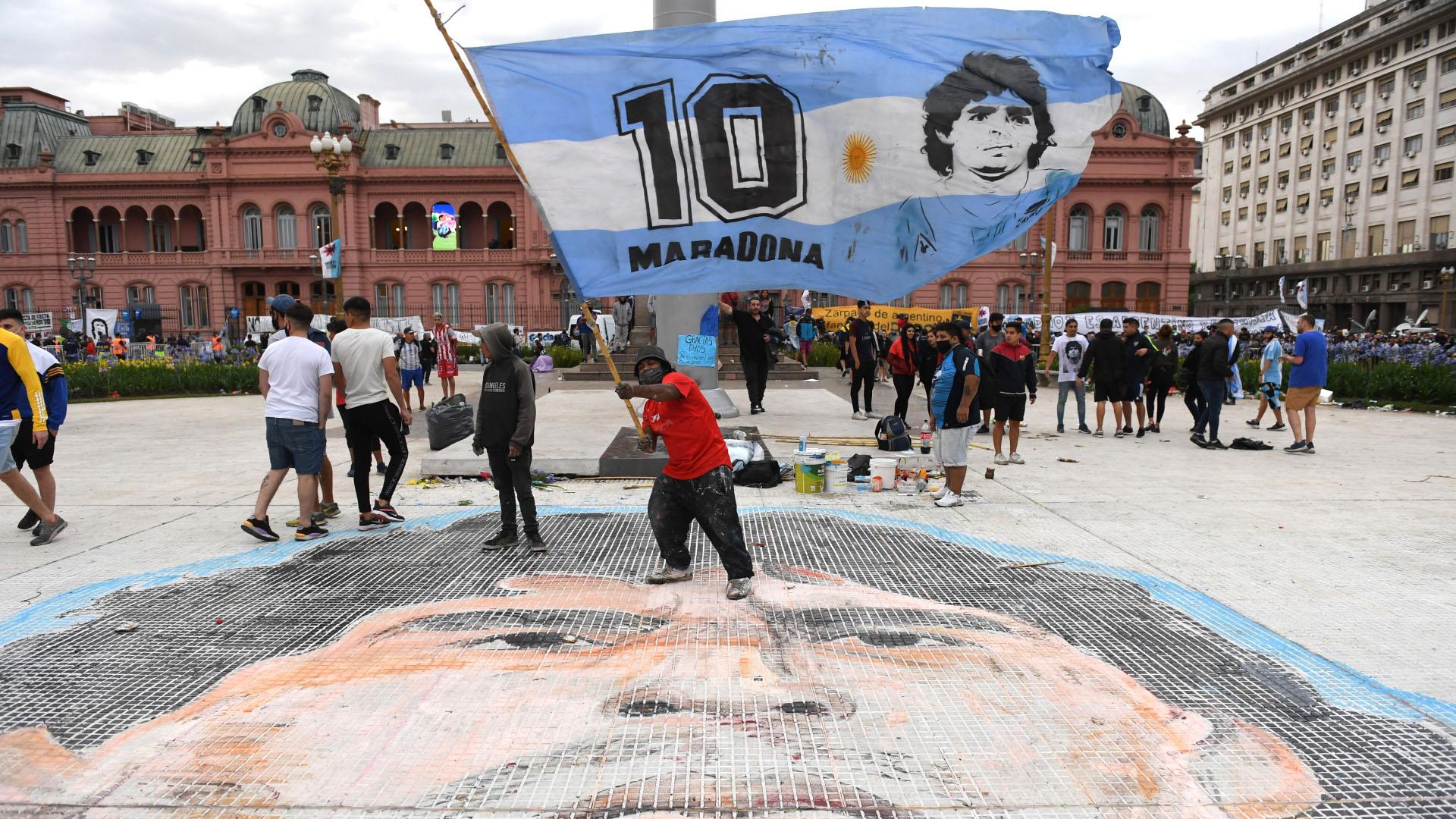 Esta mañana, cuando la gente comenzó a llegar cerca de las 6 para despedir los restos de Diego, se encontró en la Plaza de Mayo, frente a la pirámide, con un enorme retrato de Maradona pintado sobre el suelo.