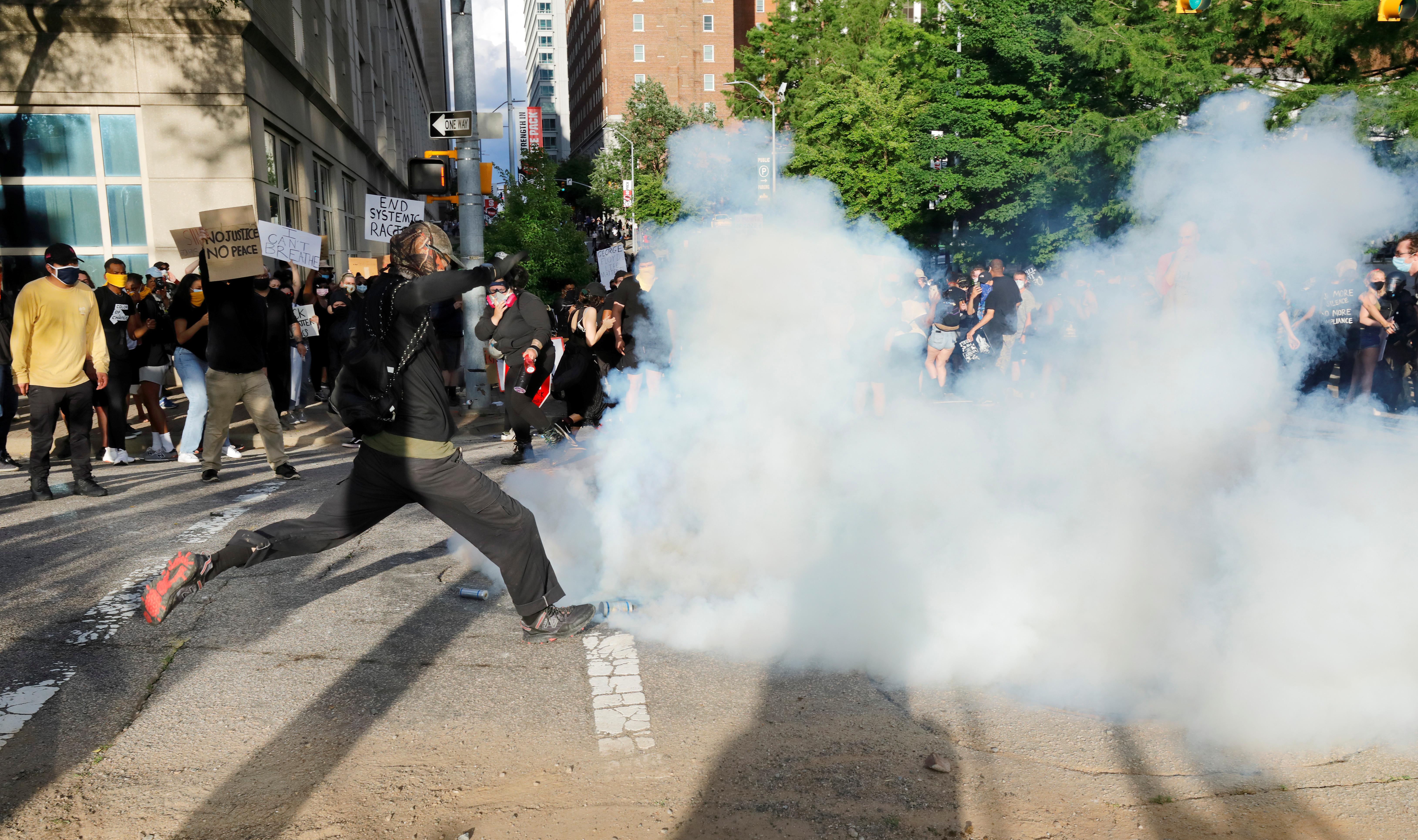 Un manifestante patea una lata de gas lacrimógeno en Raleigh, Carolina del Norte