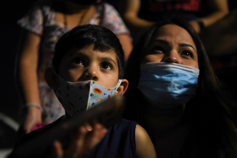 Una madre con su hijo usan tapabocas y ven los fuegos artificiales