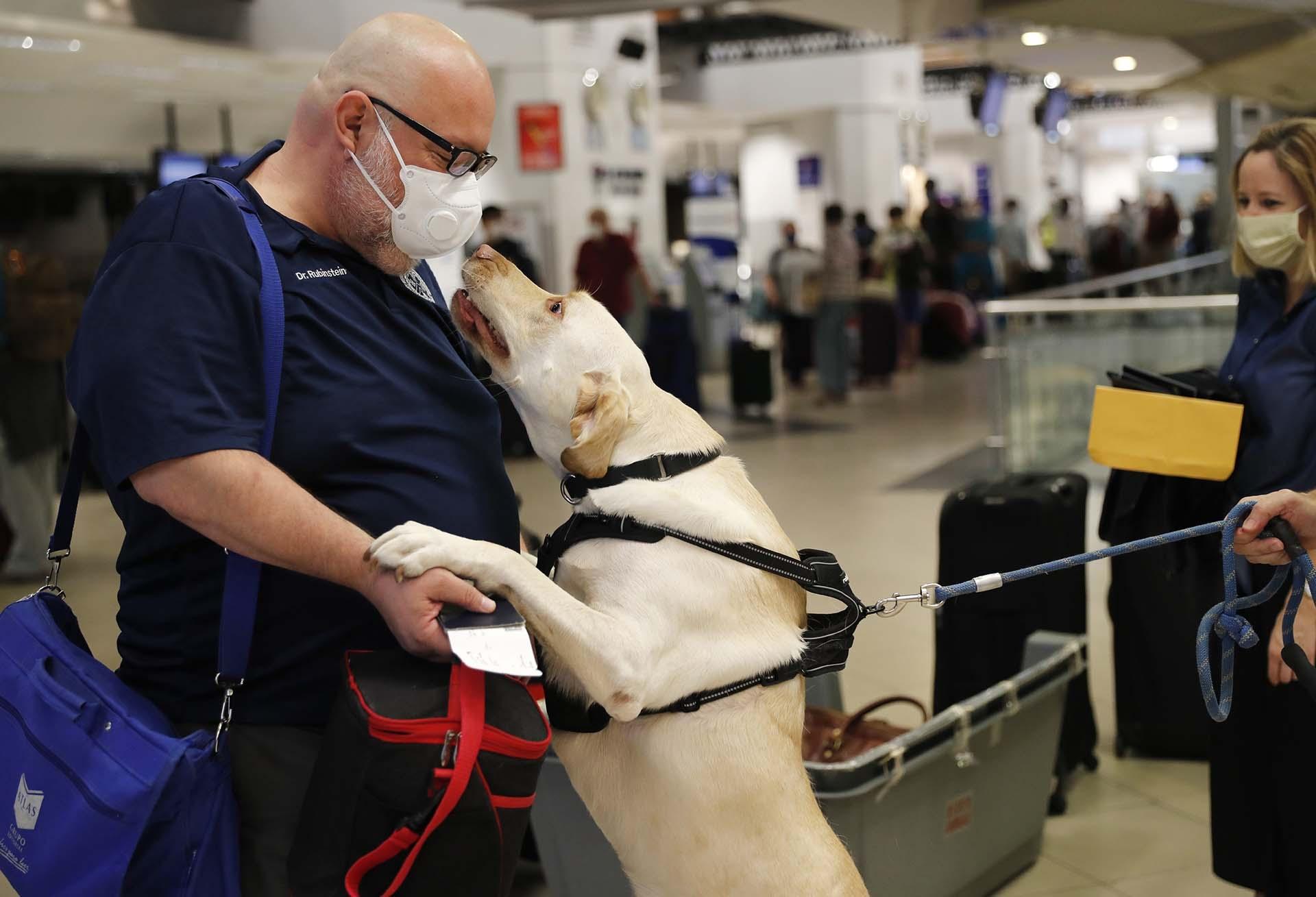El doctor Rubinstein recibe un salido de un perro llamado Dumas mientras los pasajeros se preparan para tomar un vuelo a Miami desde el aeropuerto de Asuncion, Paraguay (AP Photo/Jorge Saenz)