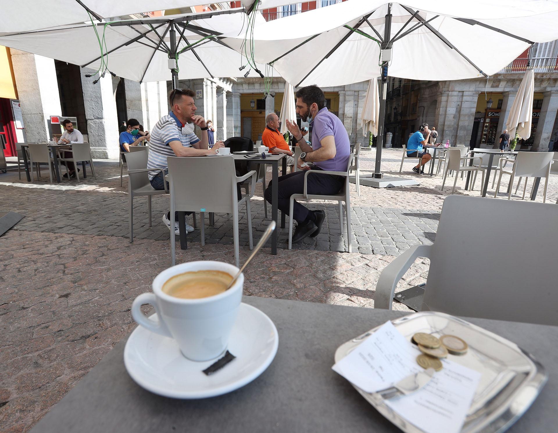 Varias personas disfrutan de la terraza de un bar de la Plaza Mayor en Madrid este lunes, donde comienza la fase 1 en la que la reapertura de las terrazas de los bares a un 50 % de su aforo y el acceso a los grandes parques son dos las principales novedades de esta nueva etapa. (EFE/Kiko Huesca)