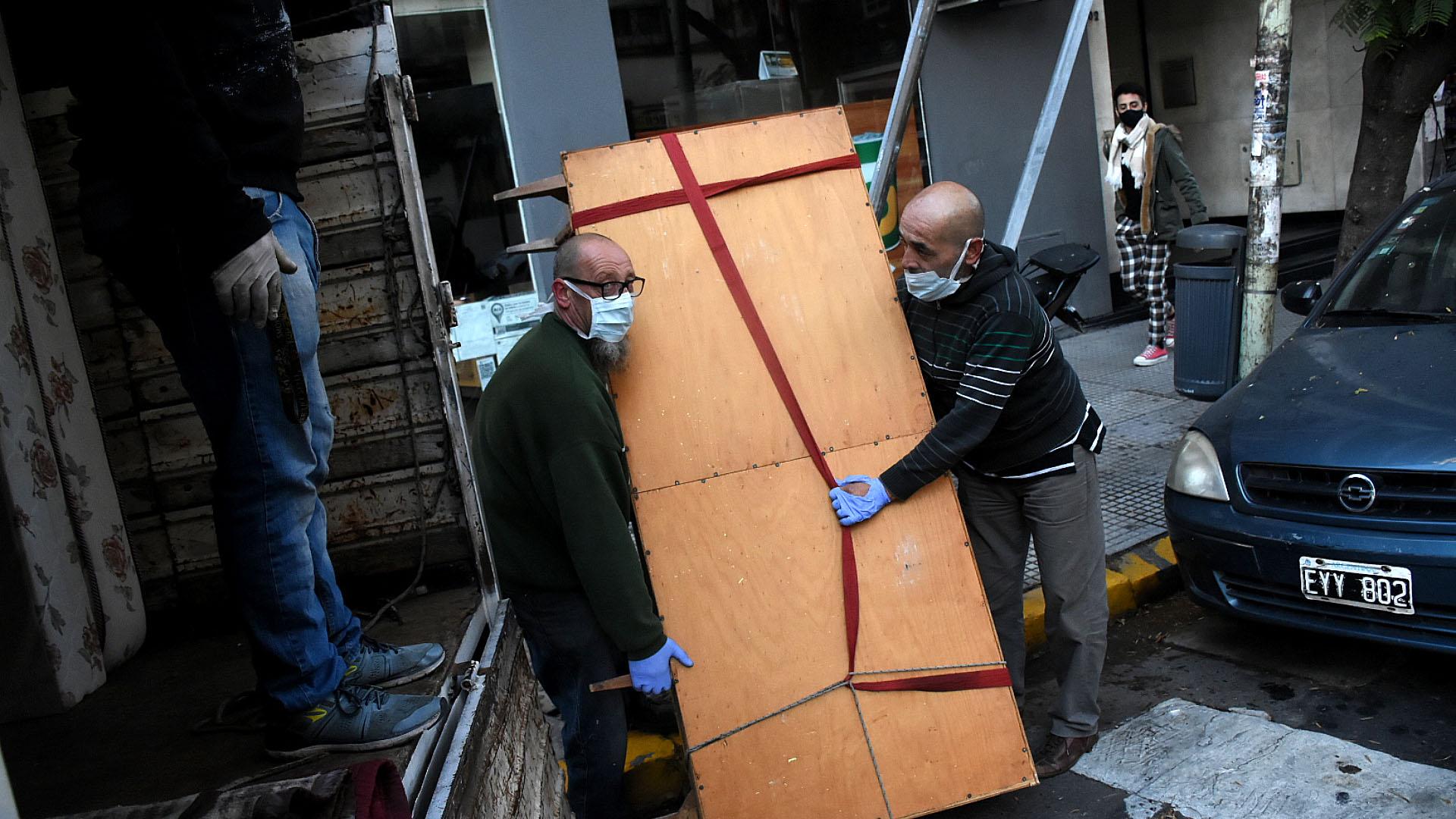 Dos empleados de una empresa de mudanza en el primer día de la reapertura de esta actividad