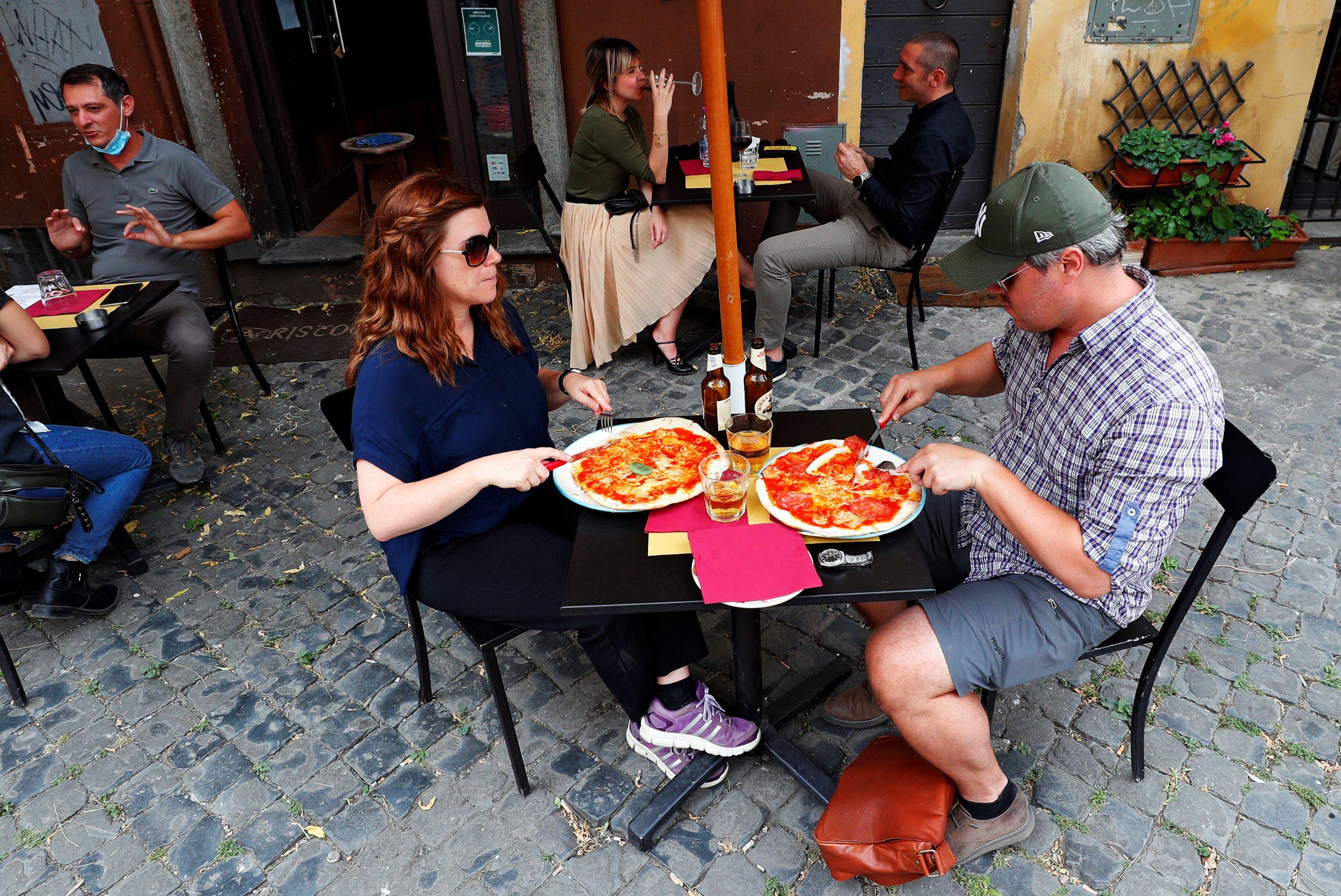 Dos personas comen una pizza en Trastevere, en Roma (Reuters/ Guglielmo Mangiapane)