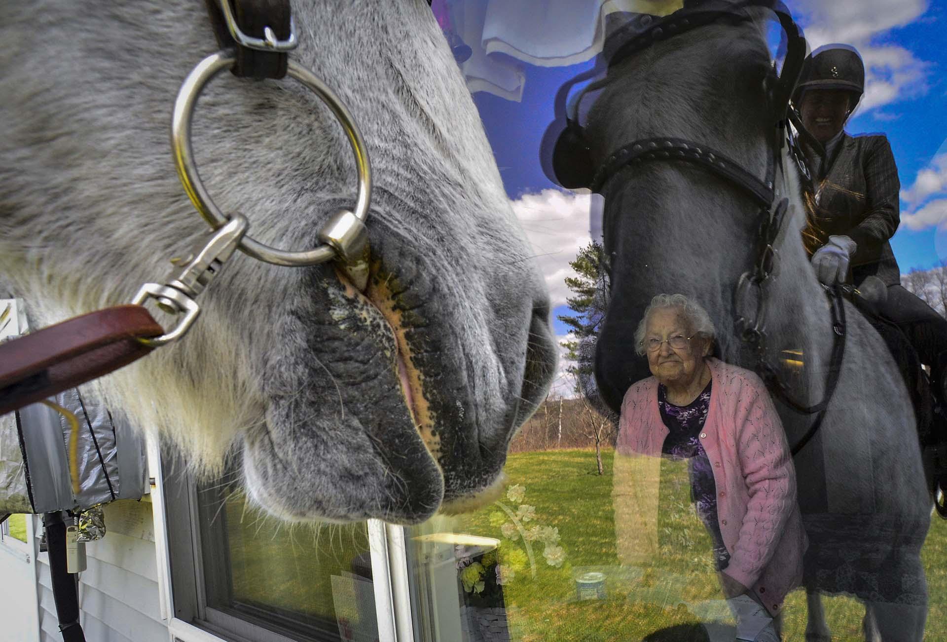 Una residente de un hogar para mayores en Vermont mira por la ventana mientras una mujer se acerca montando a un caballo (Kristopher Radder/The Brattleboro Reformer via AP)