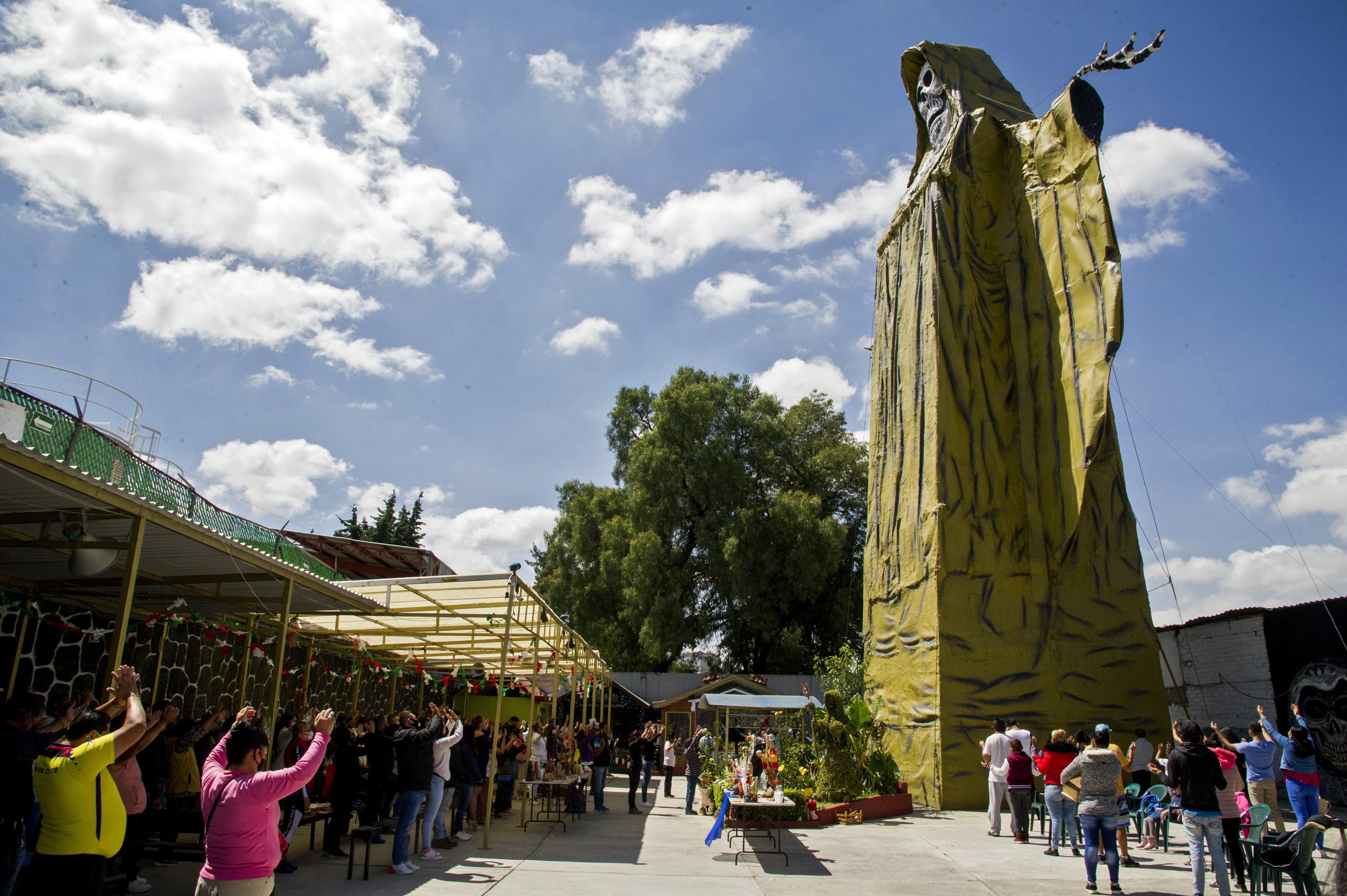 Los devotos levantan los brazos junto a una figura de la Santa Muerte de 22 metros de altura durante una ceremonia en el Santuario Internacional de la Santa Muerte en el municipio de Tultitlán, Estado de México, México, el 4 de octubre de 2020