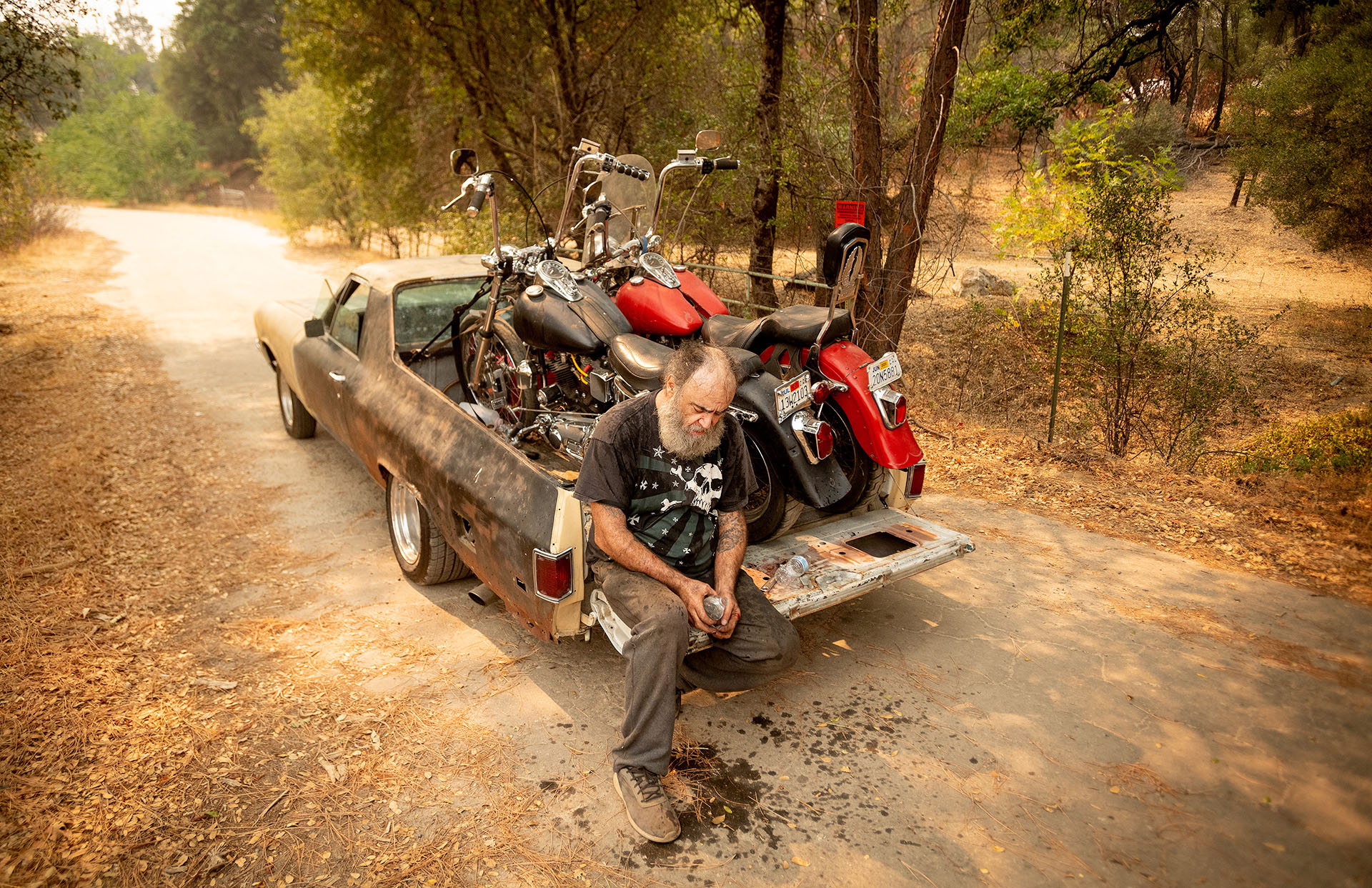 Jim Smart descansa en la parte trasera de su vehículo después de evacuar con dos de sus preciadas motocicletas durante el incendio de Creek (Foto de JOSH EDELSON / AFP)