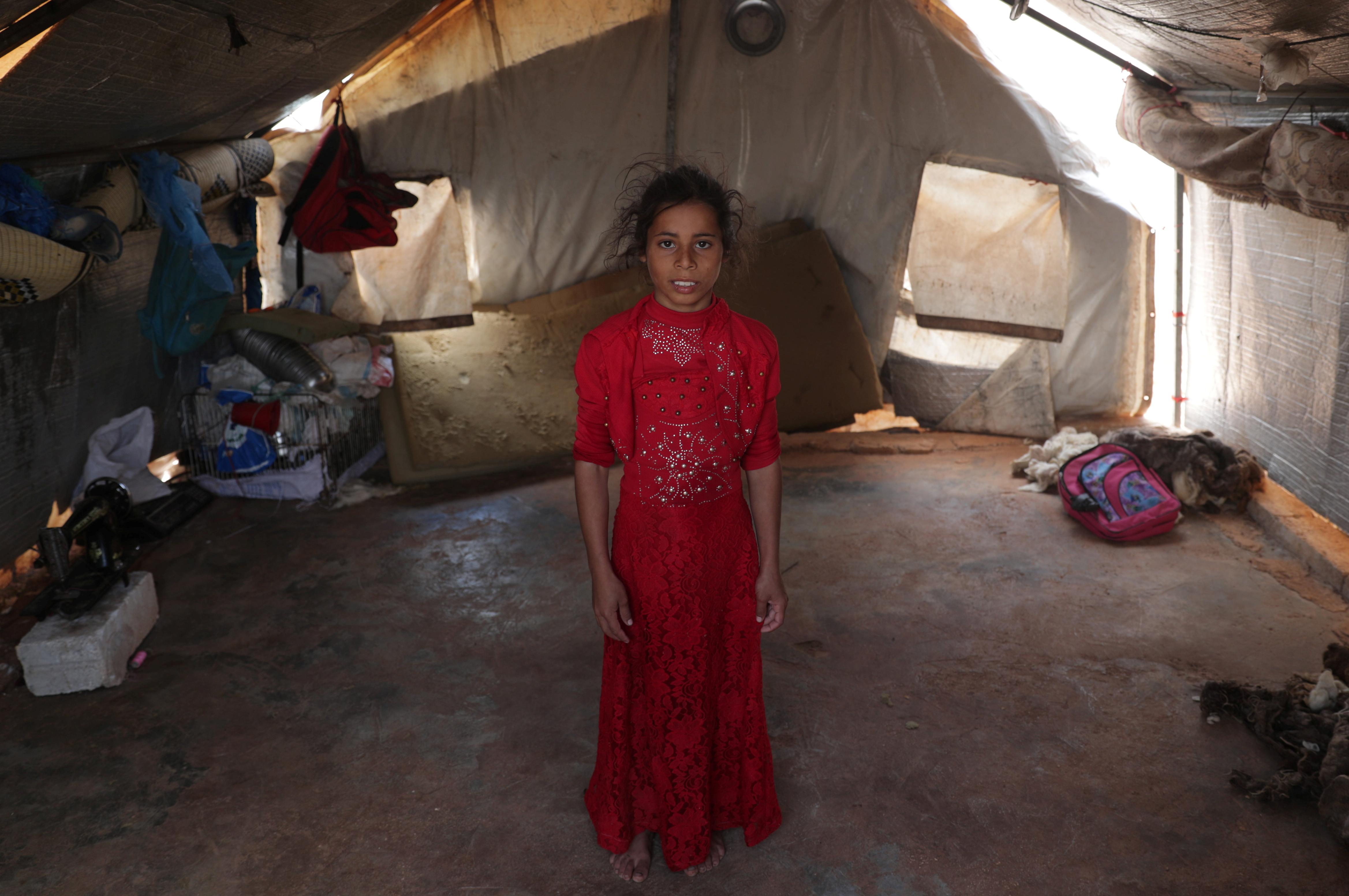 Ranim Barakat, una niña siria desplazada de nueve años del campo de Hama que nunca ha conocido la paz, sus pies descalzos asomando por debajo de un vestido rojo bordado. (REUTERS / Khalil Ashawi)