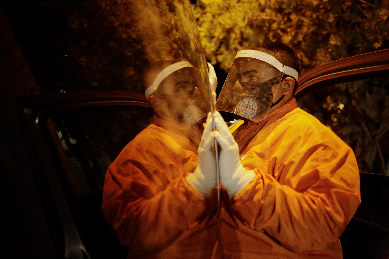 Un empleado de la funeraria Ríos espera afuera de un coche fúnebre para retirar el cuerpo de un hombre, que murió por coronavirus (COVID-19), y transportarlo a una funeraria en Ciudad Juárez, México, el 23 de octubre de 2020.