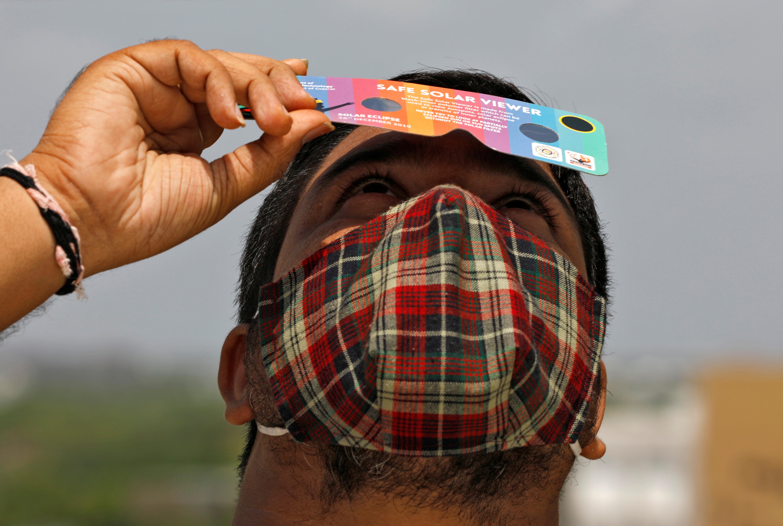 Un hombre mira el eclipse con lentes especiales de protección