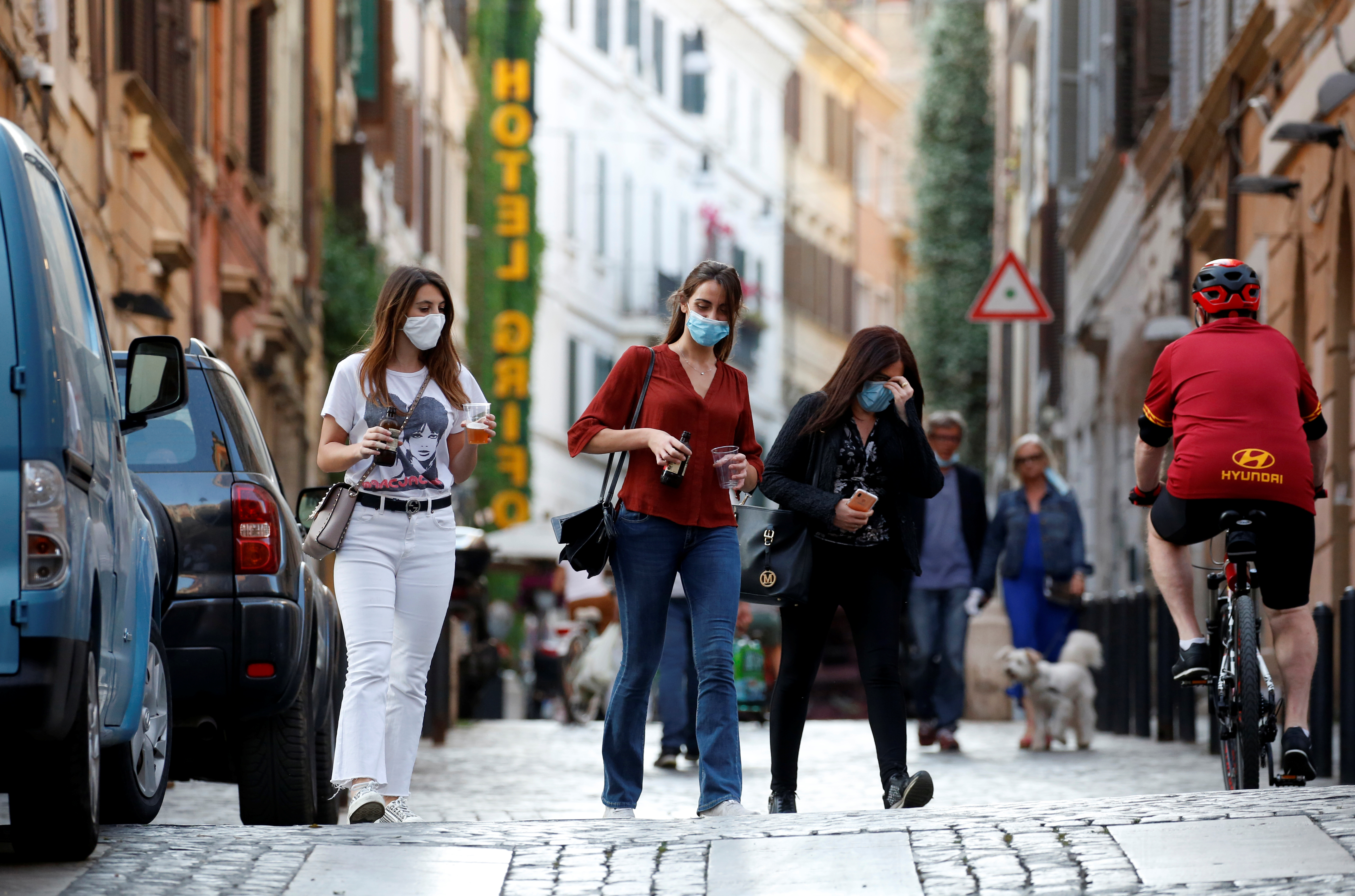 Mujeres con barbijo en el barrio Monti de Roma (REUTERS/Remo Casilli)