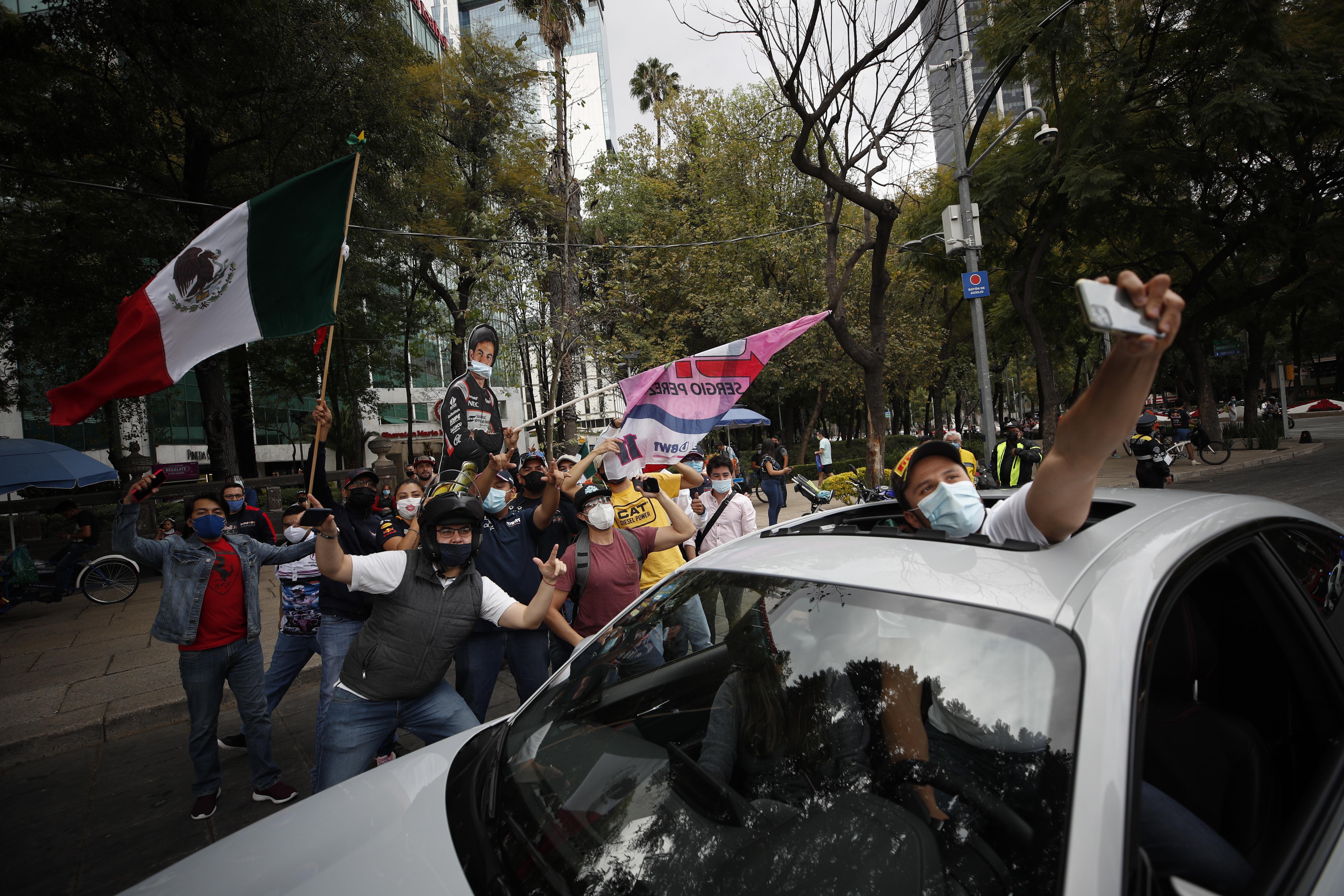 Un fan que pasa en un automóvil se detiene para posar para una foto con personas que celebran la primera victoria de Sergio