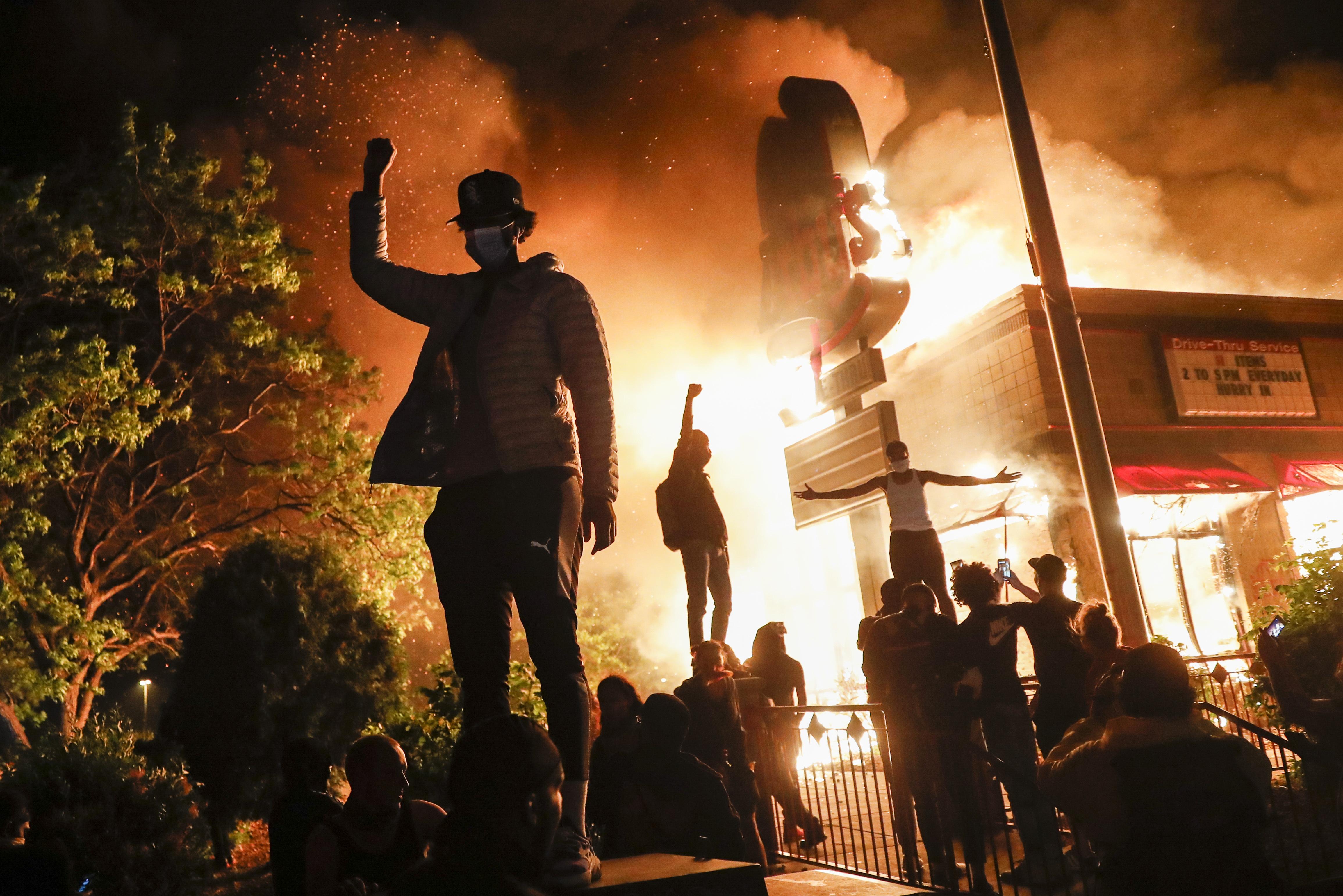 Manifestantes protestan frente a un restaurante de comida rápida en llamas, el viernes 29 de mayo de 2020, en Minneapolis (Foto AP/John Minchillo)