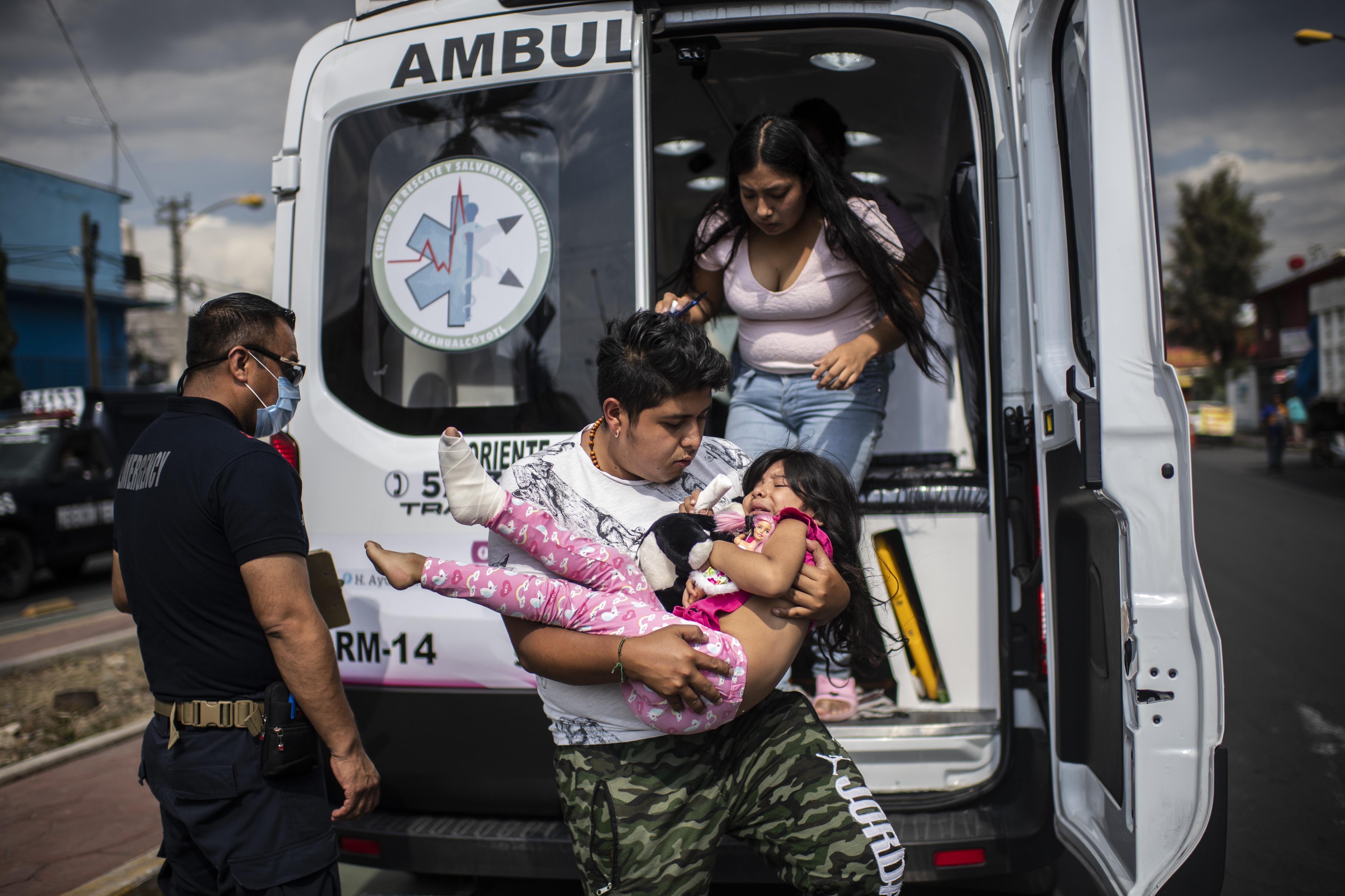 El paramédico Sergio Villafan observa cómo un hombre lleva a una niña herida en un accidente de bicicleta en Ciudad Nezahualcóyotl, Estado de México, México, el 18 de junio de 2020 durante la nueva pandemia de coronavirus de COVID-19. (Foto por Pedro PARDO / AFP)