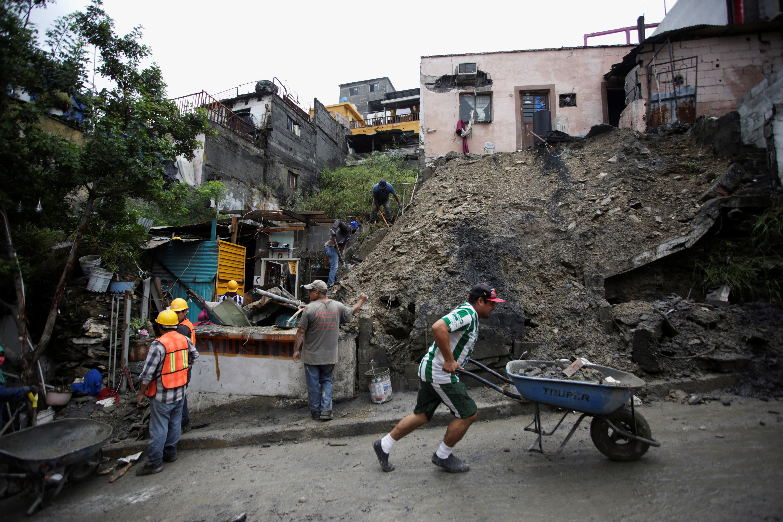 La gente trabaja para eliminar el lodo y las rocas después de un deslizamiento de tierra después de la tormenta Hanna en Monterrey, México, 27 de julio de 2020.
