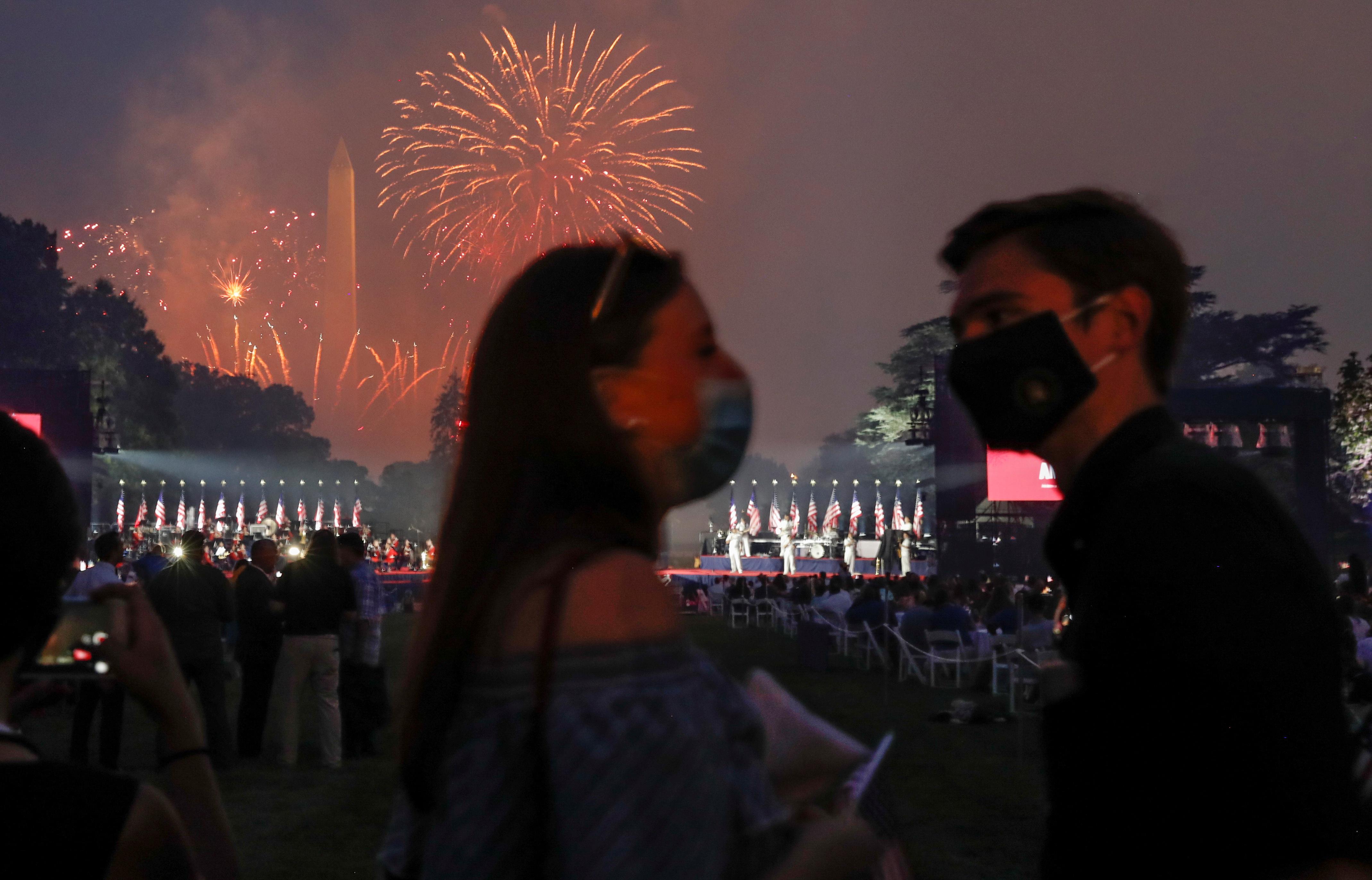 Una pareja posa para un en Washington mientras se pueden apreciar los fuegos artificiales