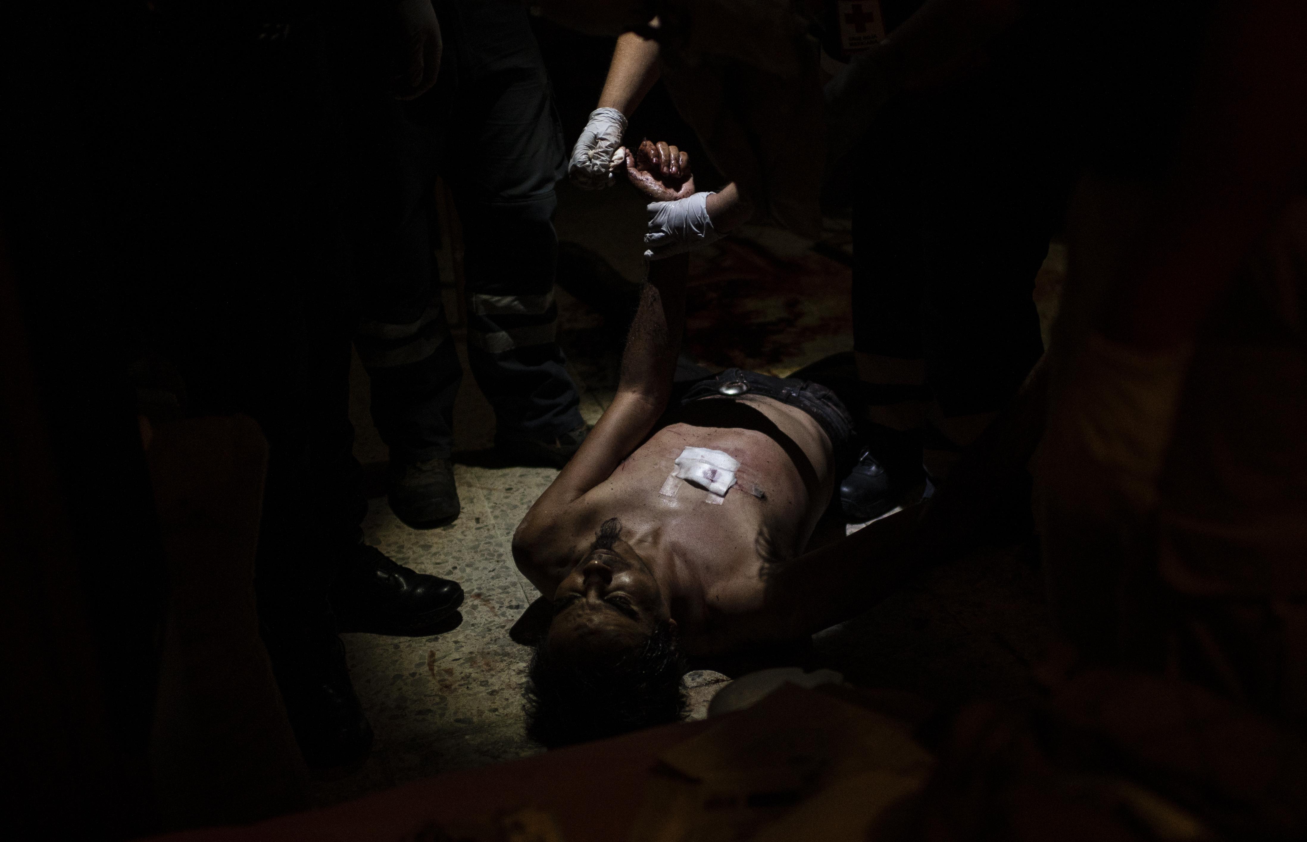 El paramédico Mydori Carmona, de 38 años, controla a un hombre que golpeó a su madre e intentó apuñalarse en el pecho, en Ciudad Nezahualcóyotl, Estado de México, México, el 20 de junio de 2020, durante la nueva pandemia de coronavirus de COVID-19. (Foto por Pedro PARDO / AFP)