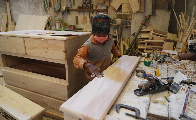 Yuri Delgado lija madera en el taller de carpintería de su familia en El Alto, Bolivia, el miércoles 2 de septiembre de 2020.