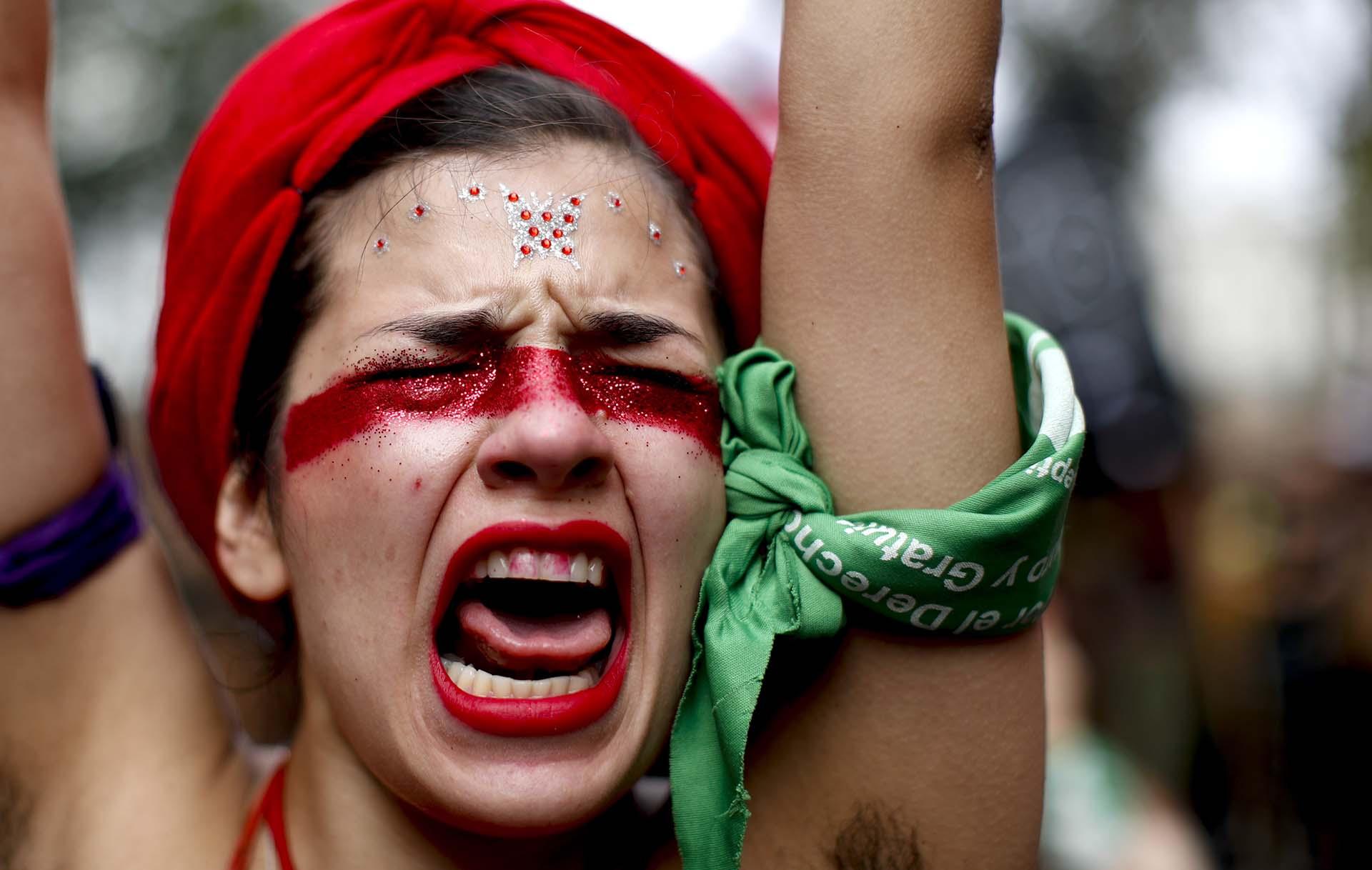Una persona grita fuerte consignas mientras marcha hacia el Congreso de la Nación para conmemorar el Día Internacional de la Mujer