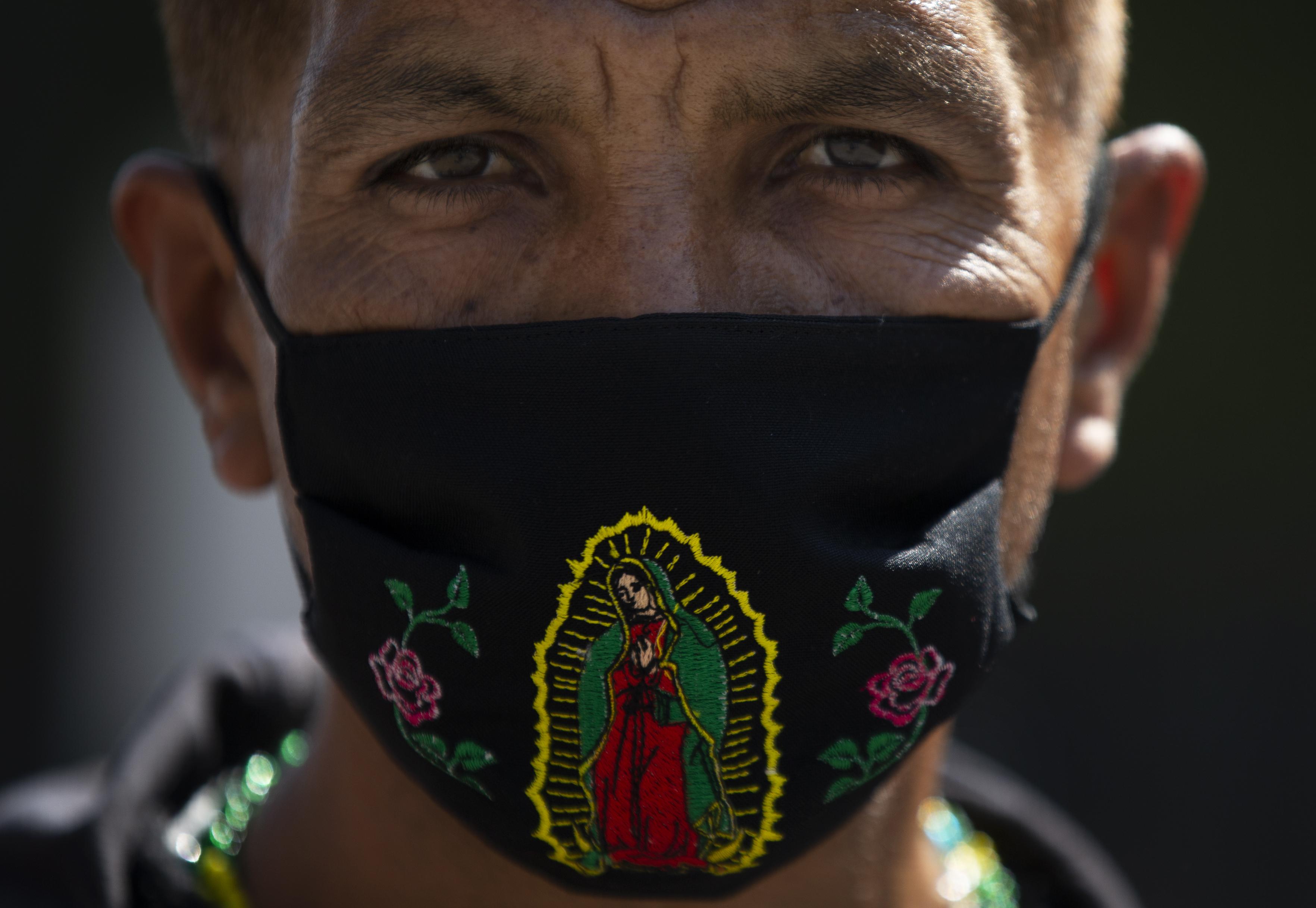 Un peregrino usa una máscara con una imagen de la Virgen de Guadalupe afuera de la Basílica de la Virgen de Guadalupe, el miércoles 9 de diciembre de 2020.