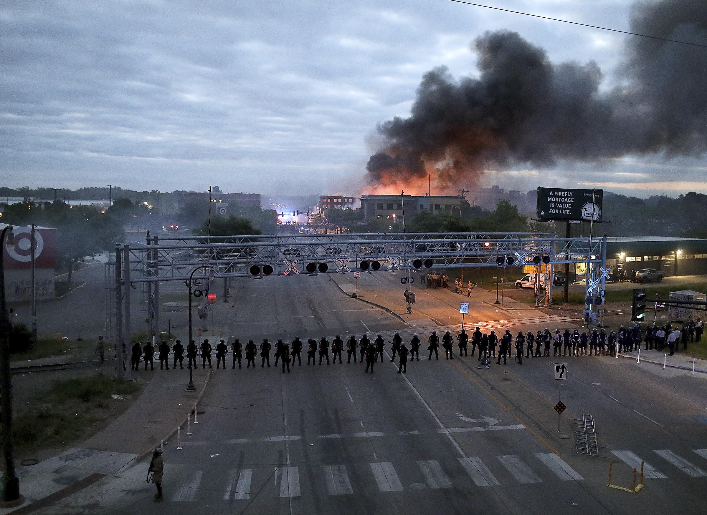 Oficiales amontonados a lo largo de la calle Lake, cerca de la avenida Hiawatha, mientras arden edificios después de una noche de disturbios y protestas por la muerte de George Floyd el viernes 29 de mayo de 2020 (David Joles/Star Tribune vía AP)