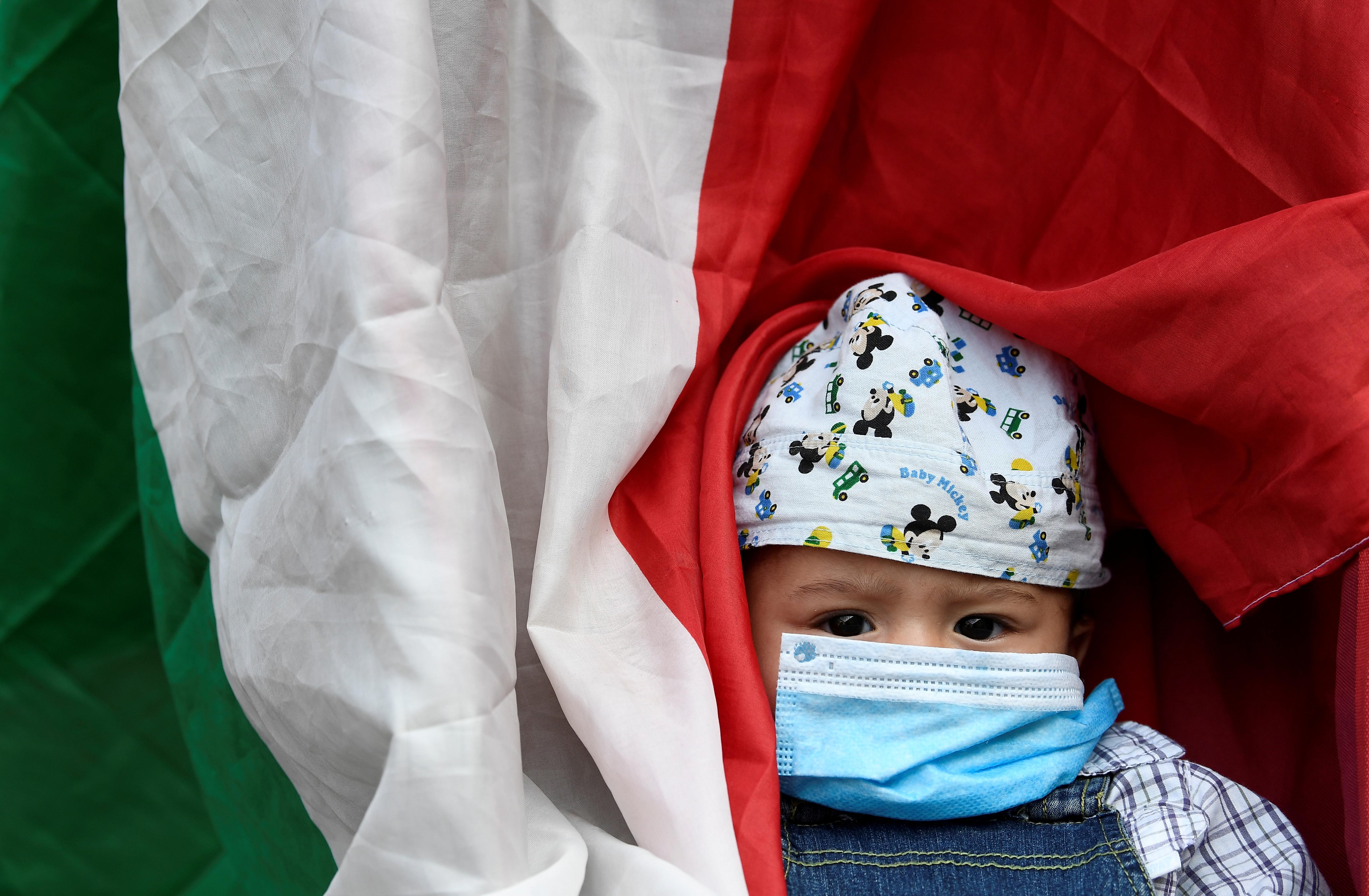 Un niño con babrijo durante una protesta frente al municipio de Milán (Reuters/ Flavio Lo Scalzo)
