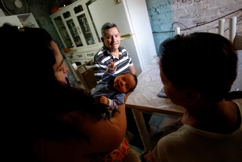 Jesús Carlos López mira a su hija Karla López Rangel, de 24 años, que tuvo un parto en casa durante el brote de la enfermedad por coronavirus (COVID-19), mientras sostiene a su hijo recién nacido Sabino Yoehi Flores López junto a la madre de Karla, Maria Rangel Soriana, en Iztapalapa, Ciudad de México, México, 4 de junio de 2020. Foto: REUTERS / Gustavo Graf.